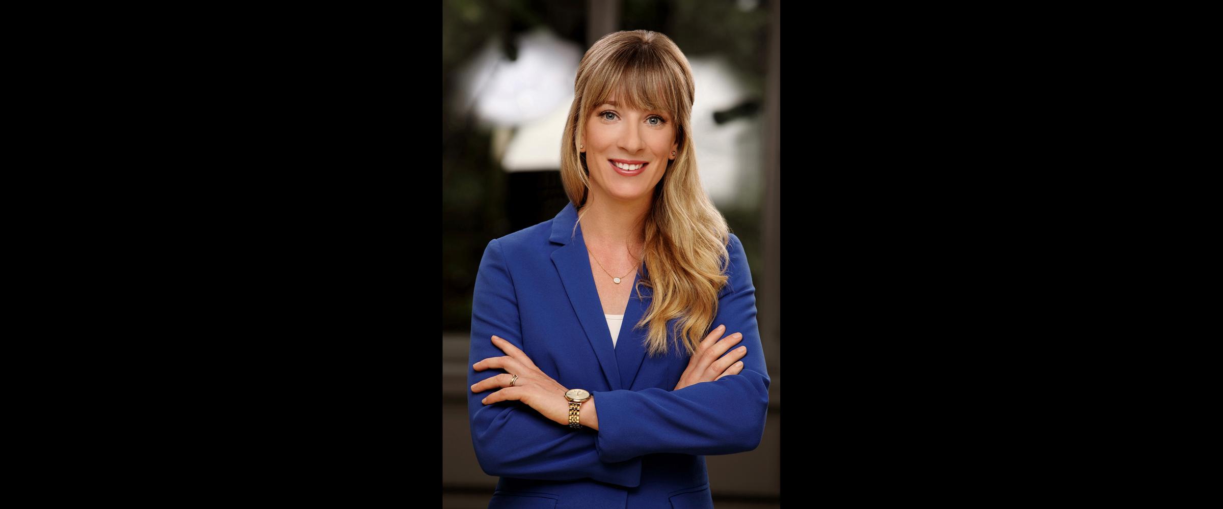 Bewerbungsfoto und Business Portrait einer blonden Frau mit blauem Business-Jackett, die freundlich lächelt und ihre Arme vor der Brust kreuzt.