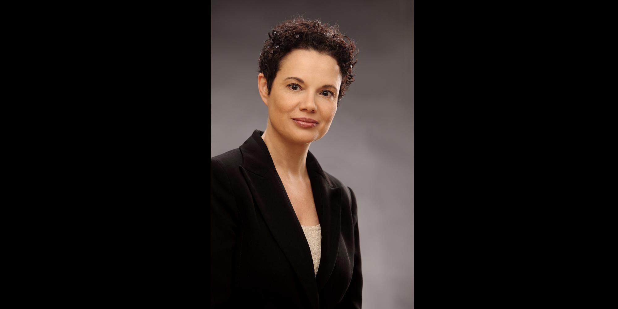 Farbportrait einer Frau mit dunklen, kurzen Haaren, die in schwarzem Business-Jackett und mit neutralem Gesichtsausdruck posiert für Bewerbungsfoto.