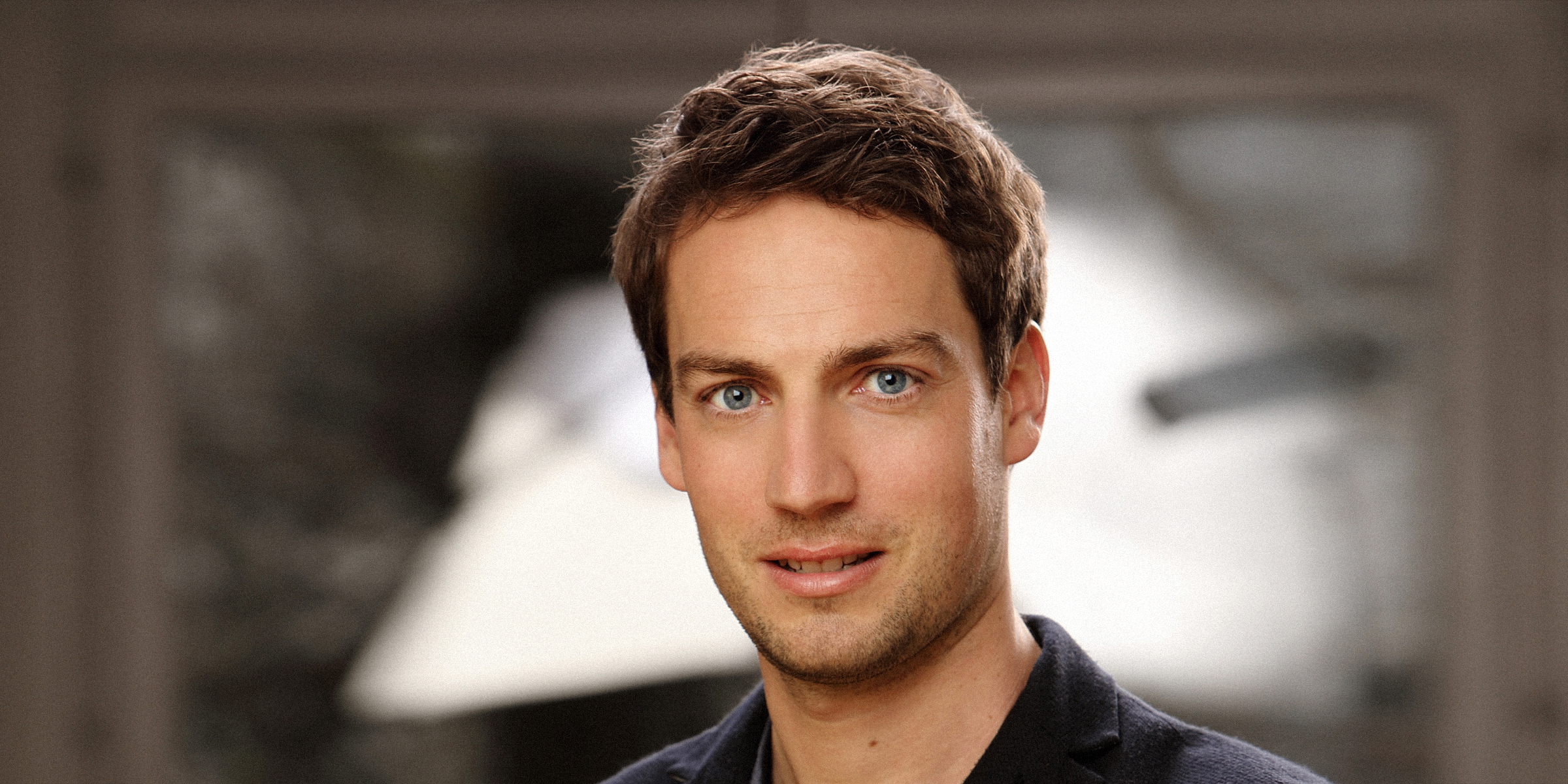 Ein Mann mit sanftem Blick posiert für Bewerbungsfoto und Portrait.