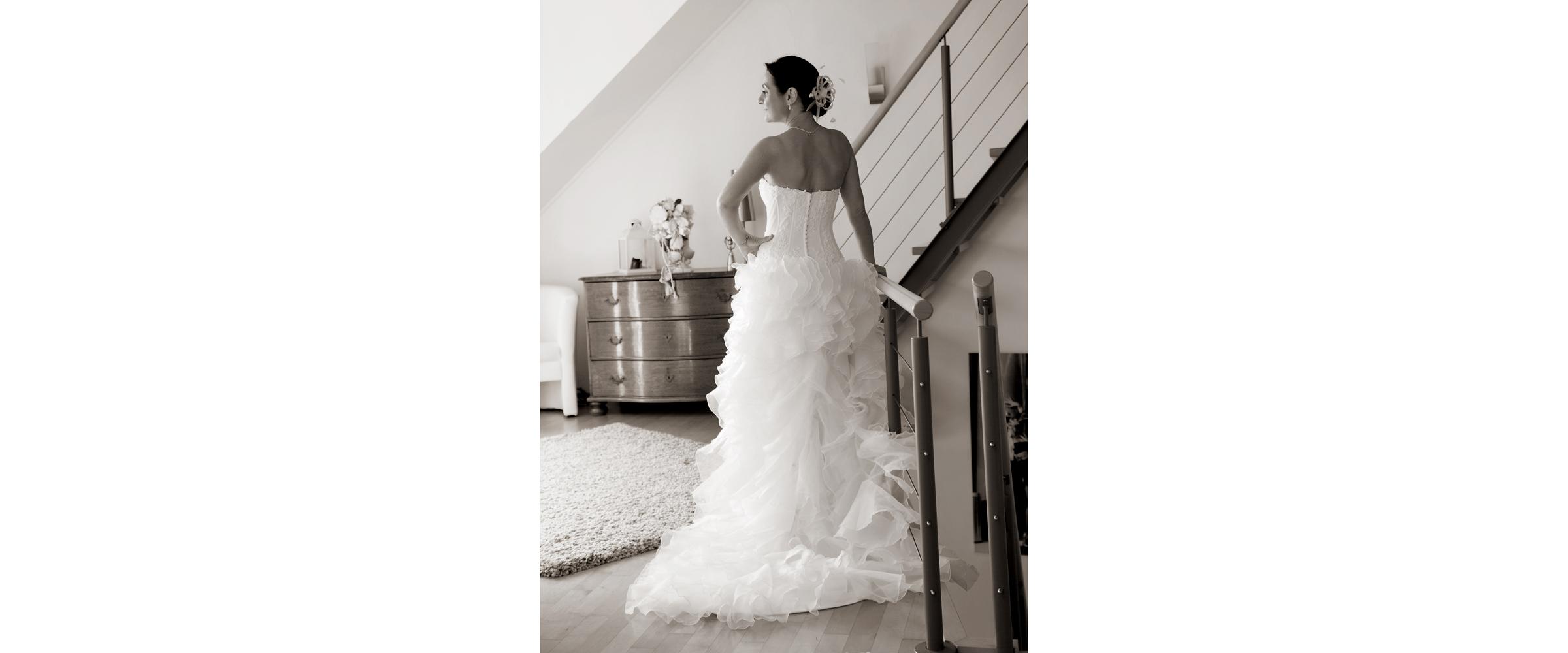 Schwarz-weiße Aufnahme der Rückenansicht einer Frau im Brautkleid, die seitlich ihre Hand in die Taille stützt und an einem Treppengeländer posiert für Hochzeitsfotografie.