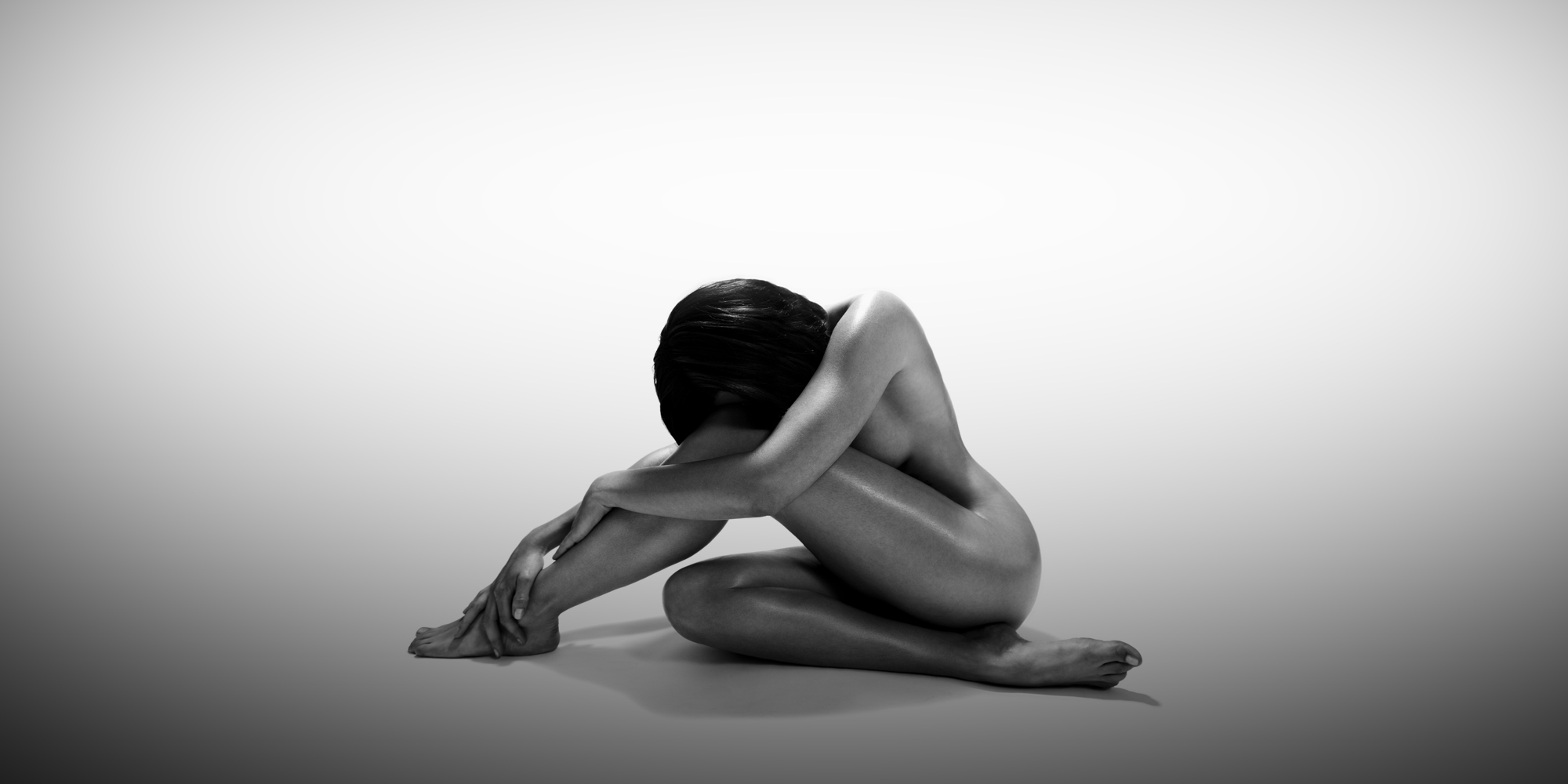 Seitliche Frontansicht einer nackten, sitzenden Frau in schwarz-weiß, die Kopf und Arme auf ihrem angewinkelten Knie abgelegt hat, sie posiert für ästhetische Aktfotografie.