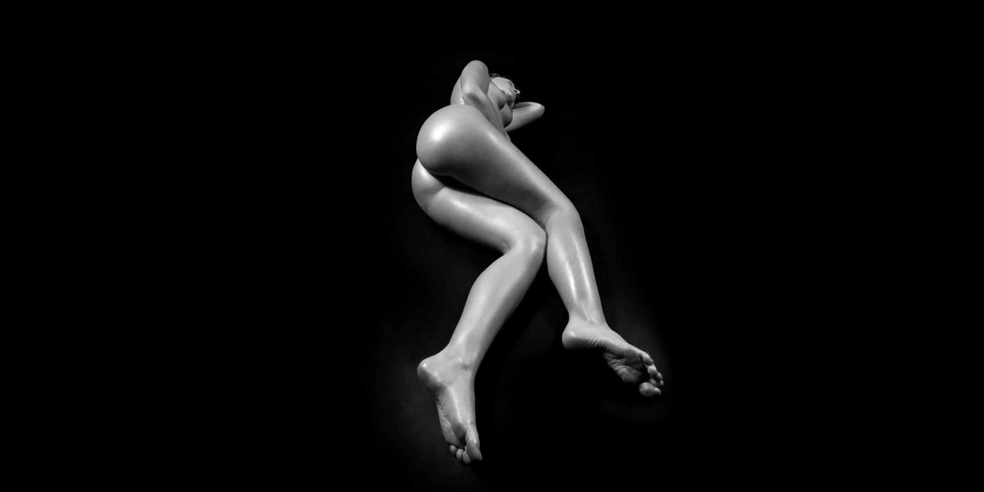 Seitliche Ansicht einer nackten, liegenden Frau in schwarz-weiß, die ihre Beine leicht angewinkelt, sie posiert für ästhetische erotische Aktfotografie.