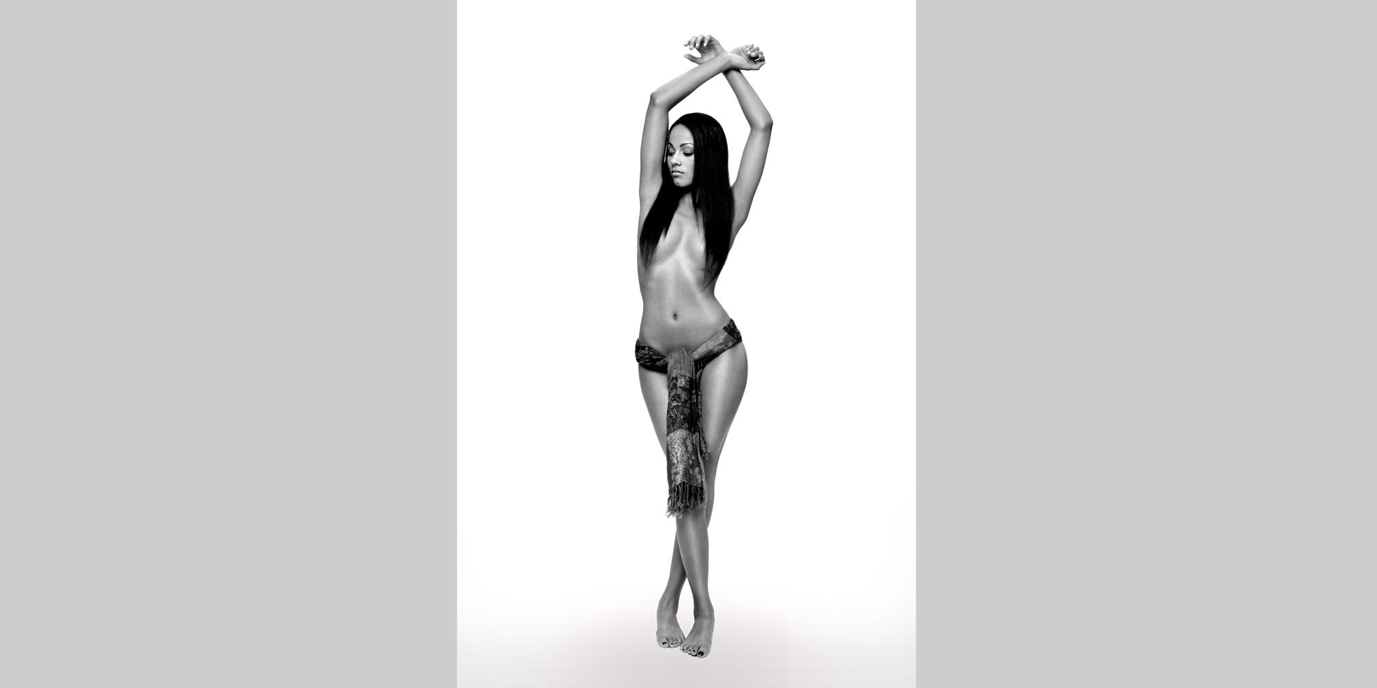 Ästhetisches erotisches Ganzkörperportrait einer nackten, exotischen Frau, deren langes Haar ihre Brust bedeckt und die einen Schal um Hüfte und Genitalien trägt.