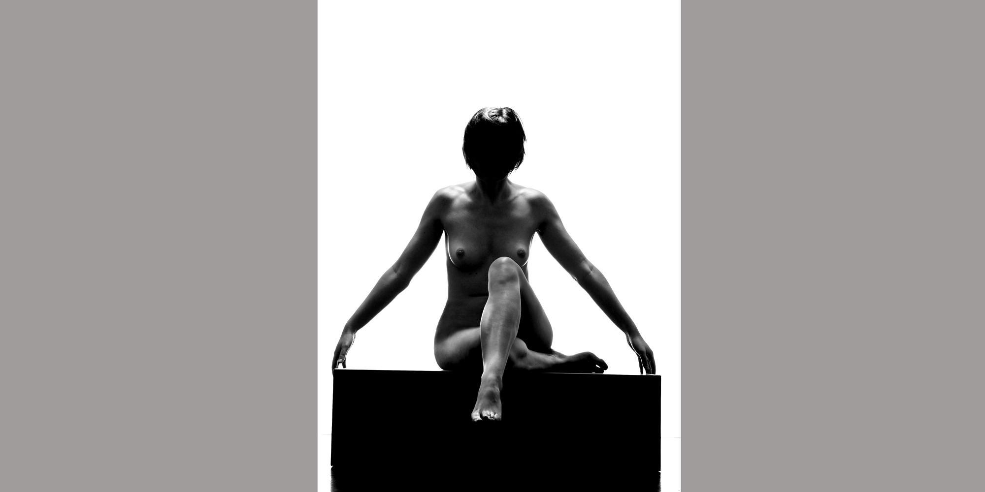 FrontanSeitliche Rückansicht in Farbe einer nackten Frau mit langem Haar, die für ästhetische Aktfotografie posiert und ein Bein anwinkelt und sich an der Wand abstützt, sie posiert für ästhetische Aktfotografie.sicht in schwarz-weiß einer nackten frau mit abgedunkelter Gesichtspartie, die ihre Beine vor sich kreuzt.