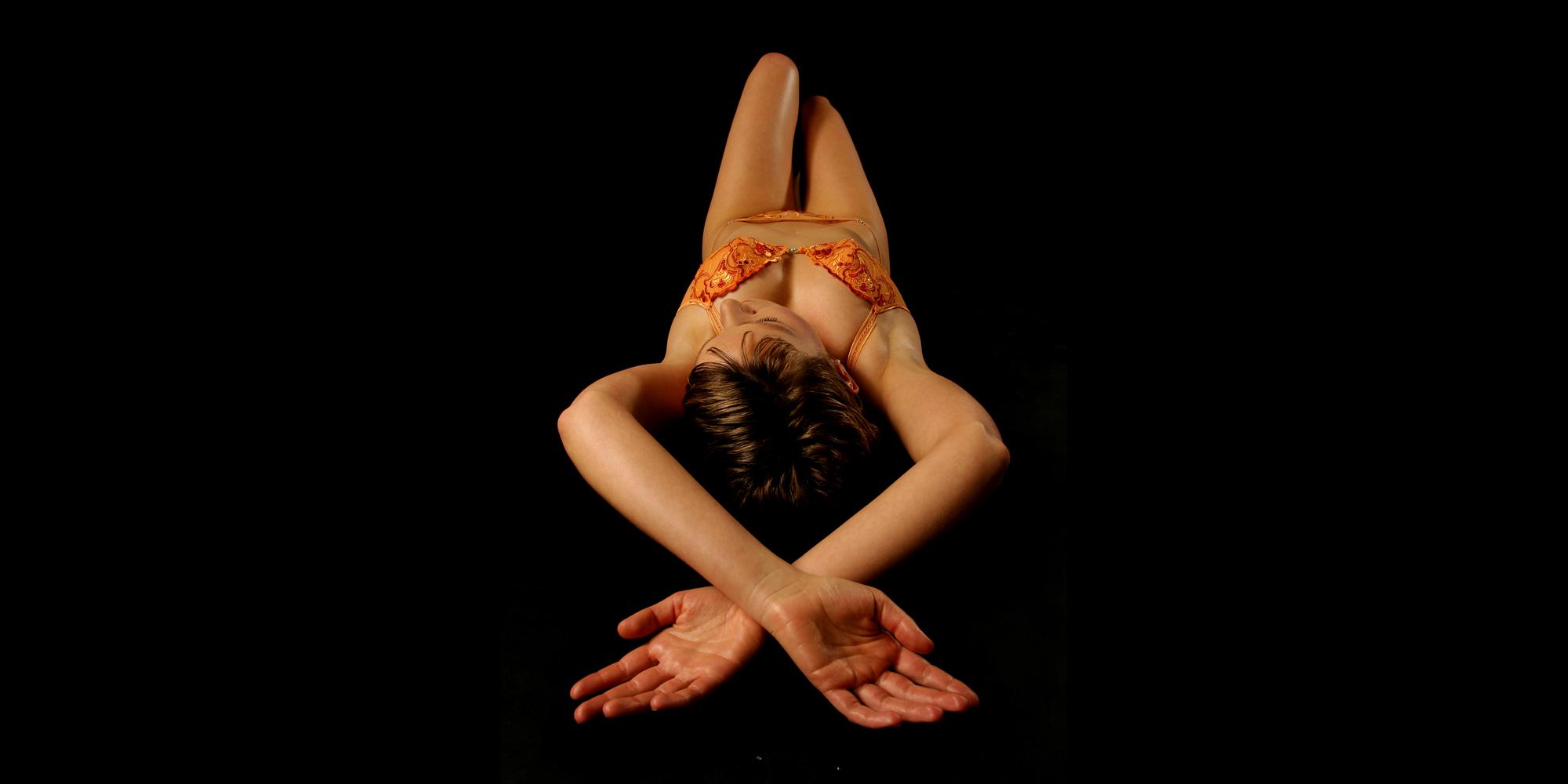 Frontansicht von oben einer liegenden Frau in erotischer Unterwäsche, die ihr Bein anwinkelt und ihre Arme über dem Kopf kreuzt.