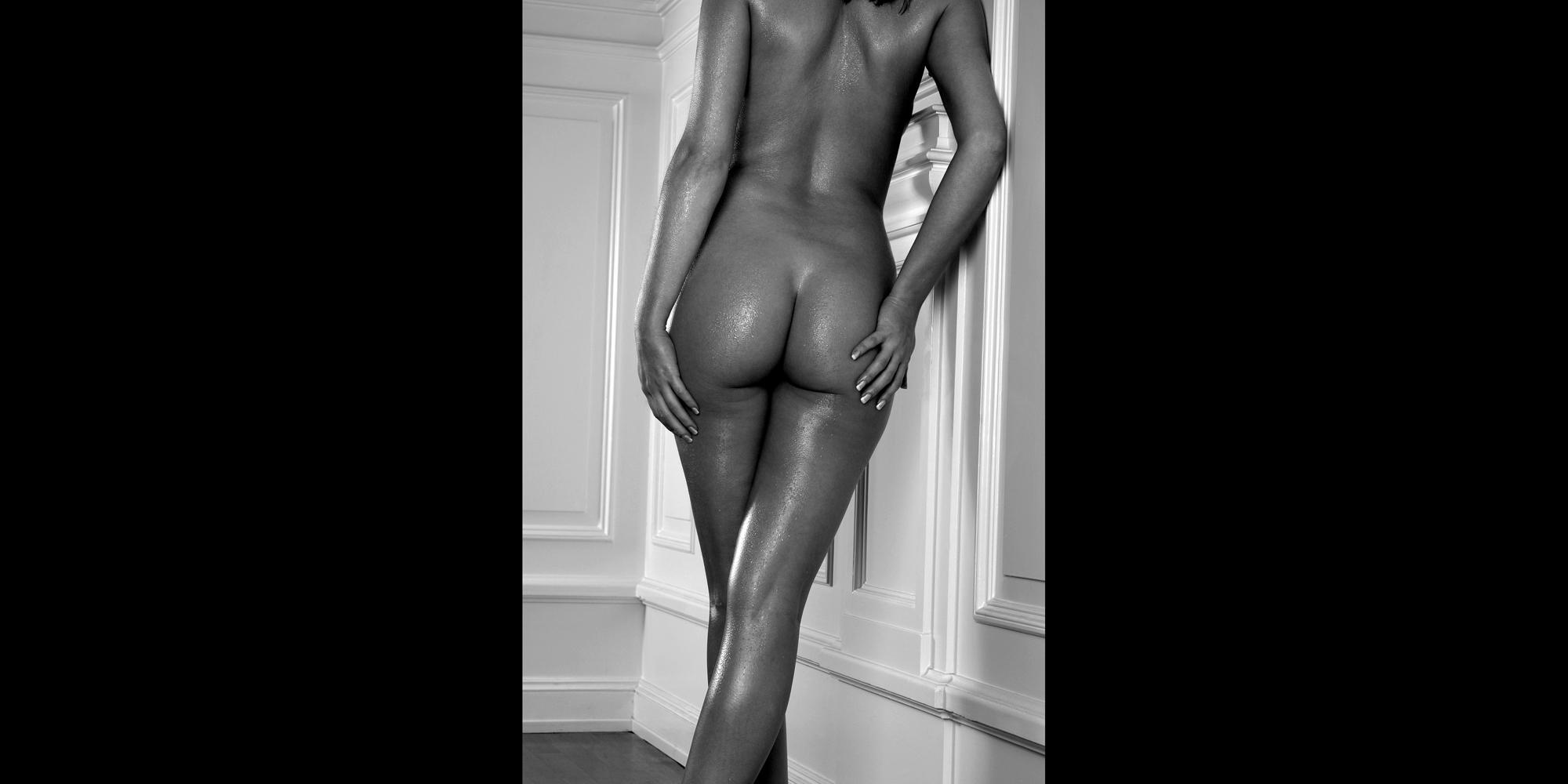 Rückansicht in Schwarz-Weiß von Po und Beinen einer nackten, schlanken Frau, deren Haut von Wasserperlen glänzt, sie posiert für ästhetische Aktfotografie.