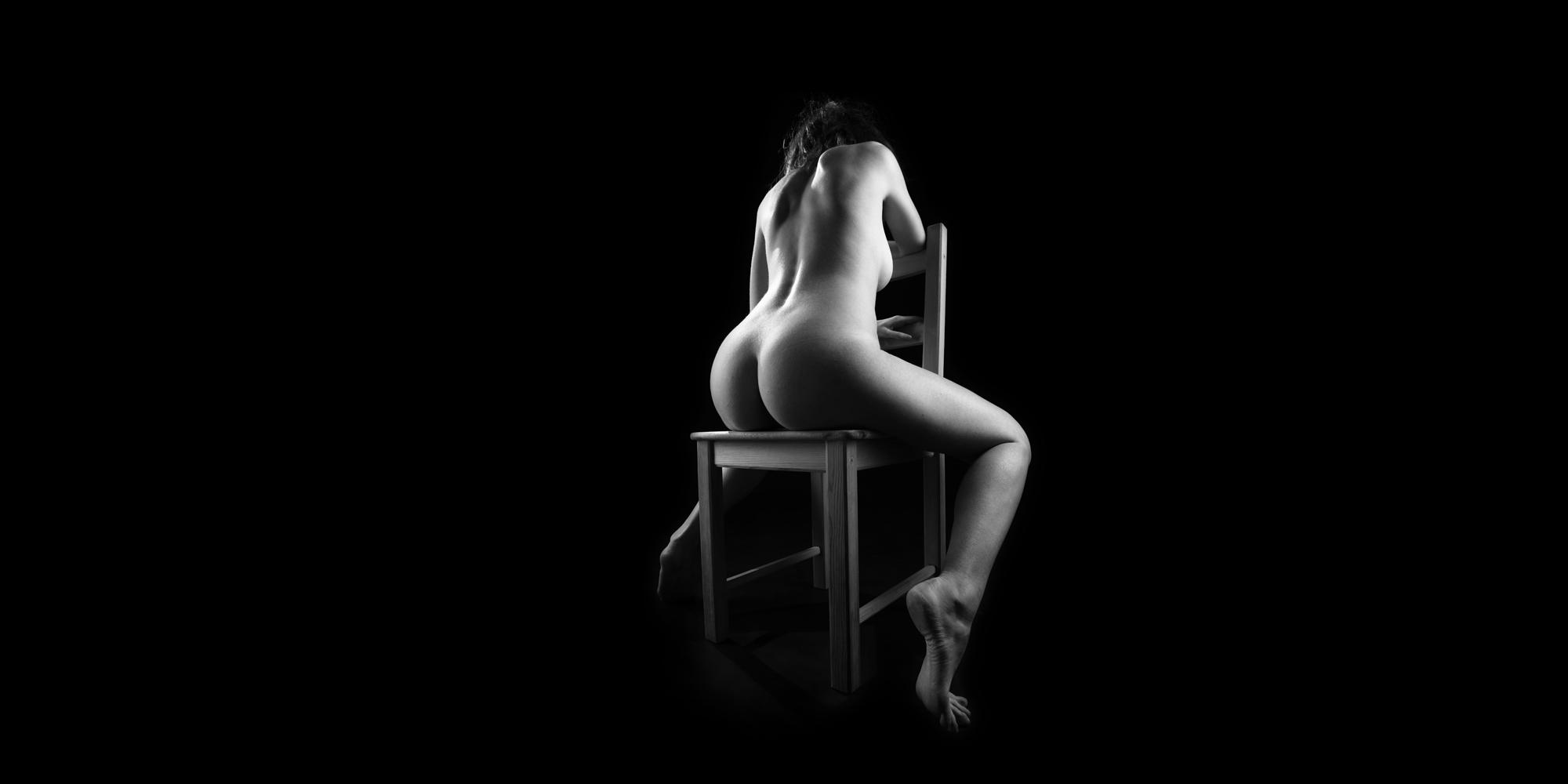 Rückansicht einer nackten Frau in schwarz-weiß, die mit gespreizten Beinen auf einem Stuhl sitzt, sie posiert für ästhetische Aktfotografie.