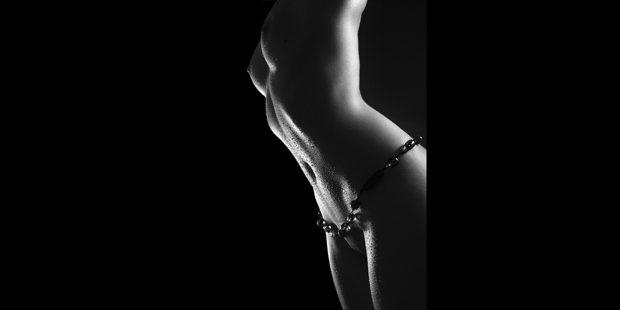 Ästhetische Aktfotografie, seitlicher Bildausschnitt in schwarz-weiß von Brust, Bauch und Genitalien einer schlanken Frau, mit perlenden Wassertropfen auf der Haut, die eine Kette um die Hüfte trägt.