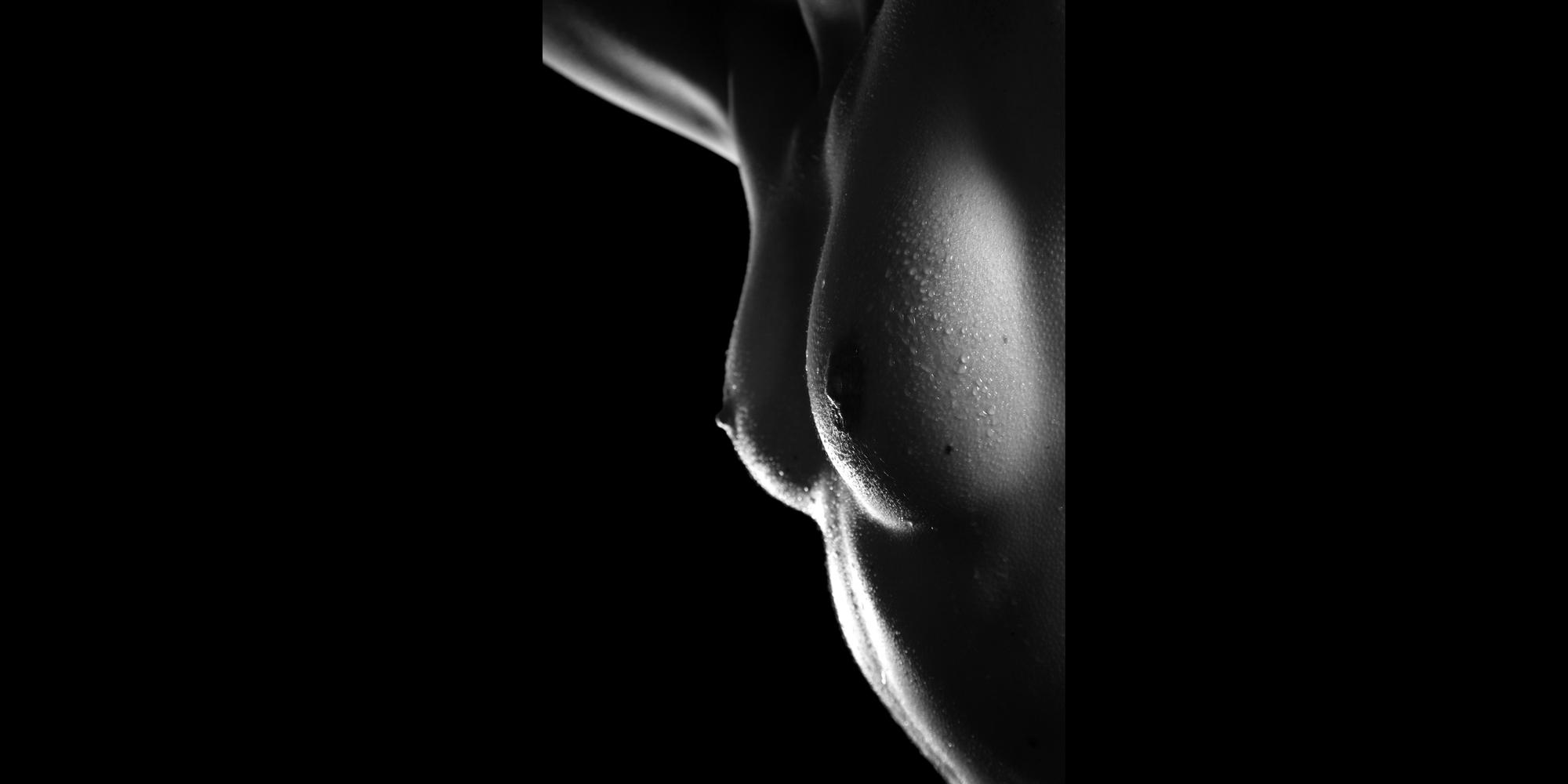 Erotischer Bildausschnitt in schwarz-weiß von der Brust einer nackten, schlanken Frau mit perlenden Wassertropfen auf der Haut.