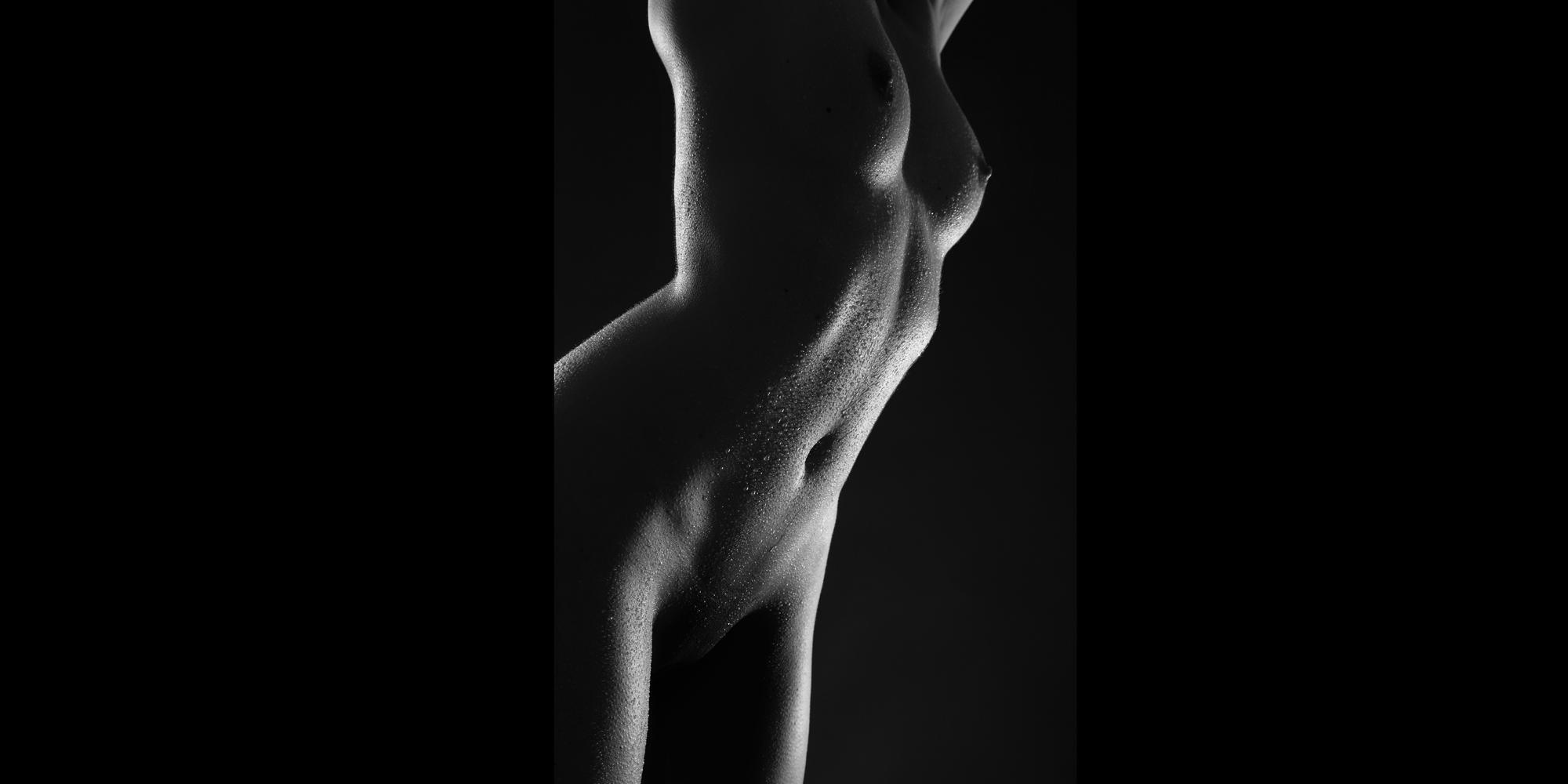 Seitlicher Bildausschnitt, ästhetische Aktfotografie in schwarz-weiß von Brust, Bauch und Genitalien einer schlanken Frau mit perlenden Wassertropfen auf der Haut.