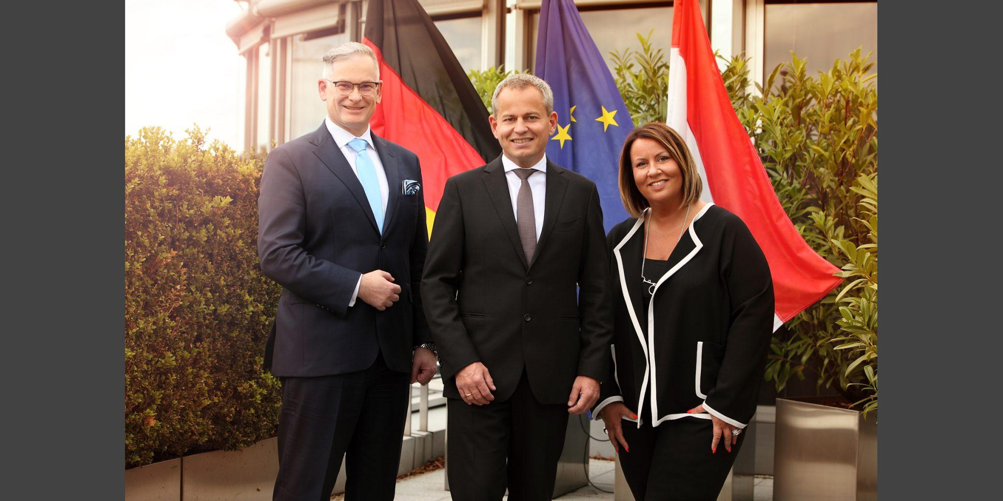 Farbaufnahme eines Mannes, der in einem schwarzen, eleganten Business-Anzug, vor dem Hintergrund dreier Fahnen und zwischen einem Mann und einer Frau von der Deutsche Bank Luxemburg posiert.
