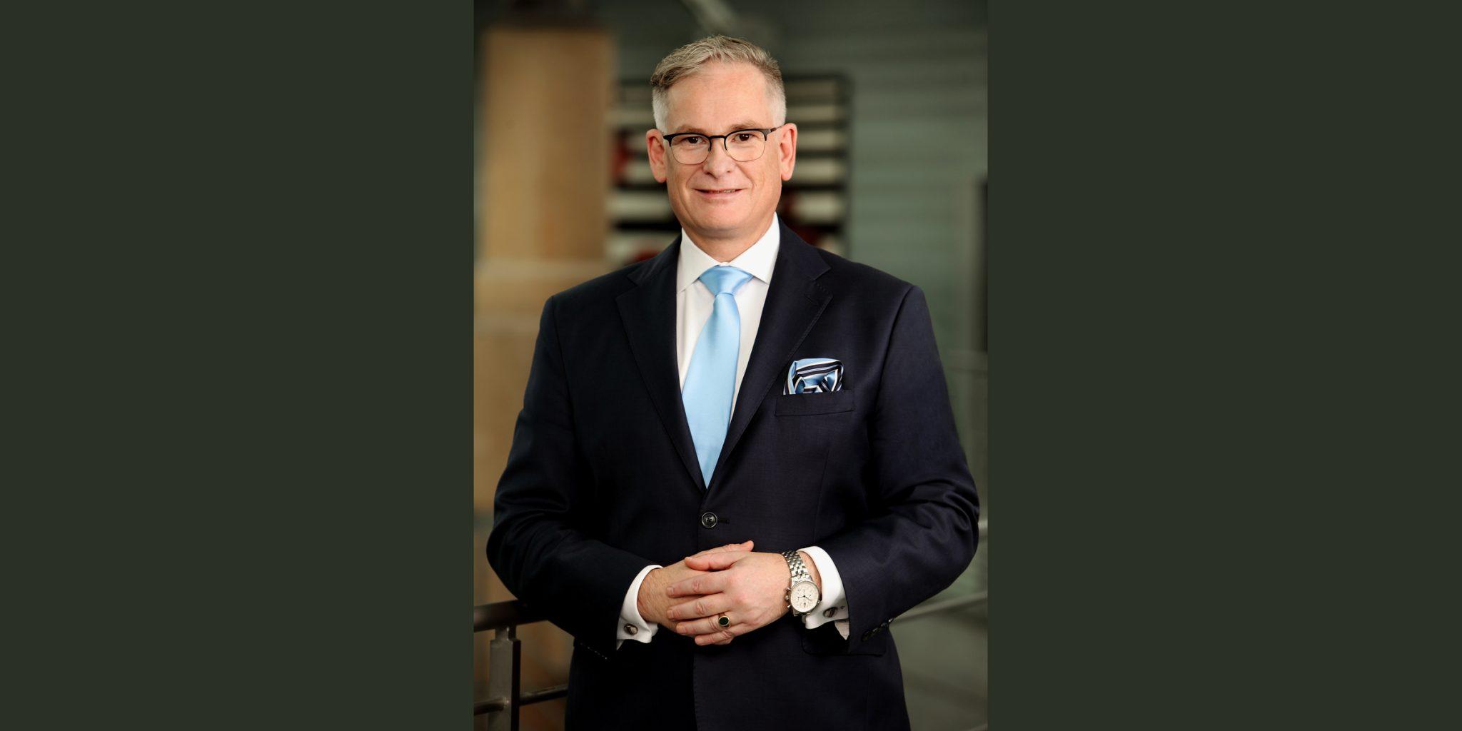 Farbportrait eines Mannes von Deutsche Bank Luxemburg mit Brille, der in einem eleganten, schwarzen Business-Anzug, hellblauer Krawatte und mit gekreuzten Händen selbstsicher posiert.