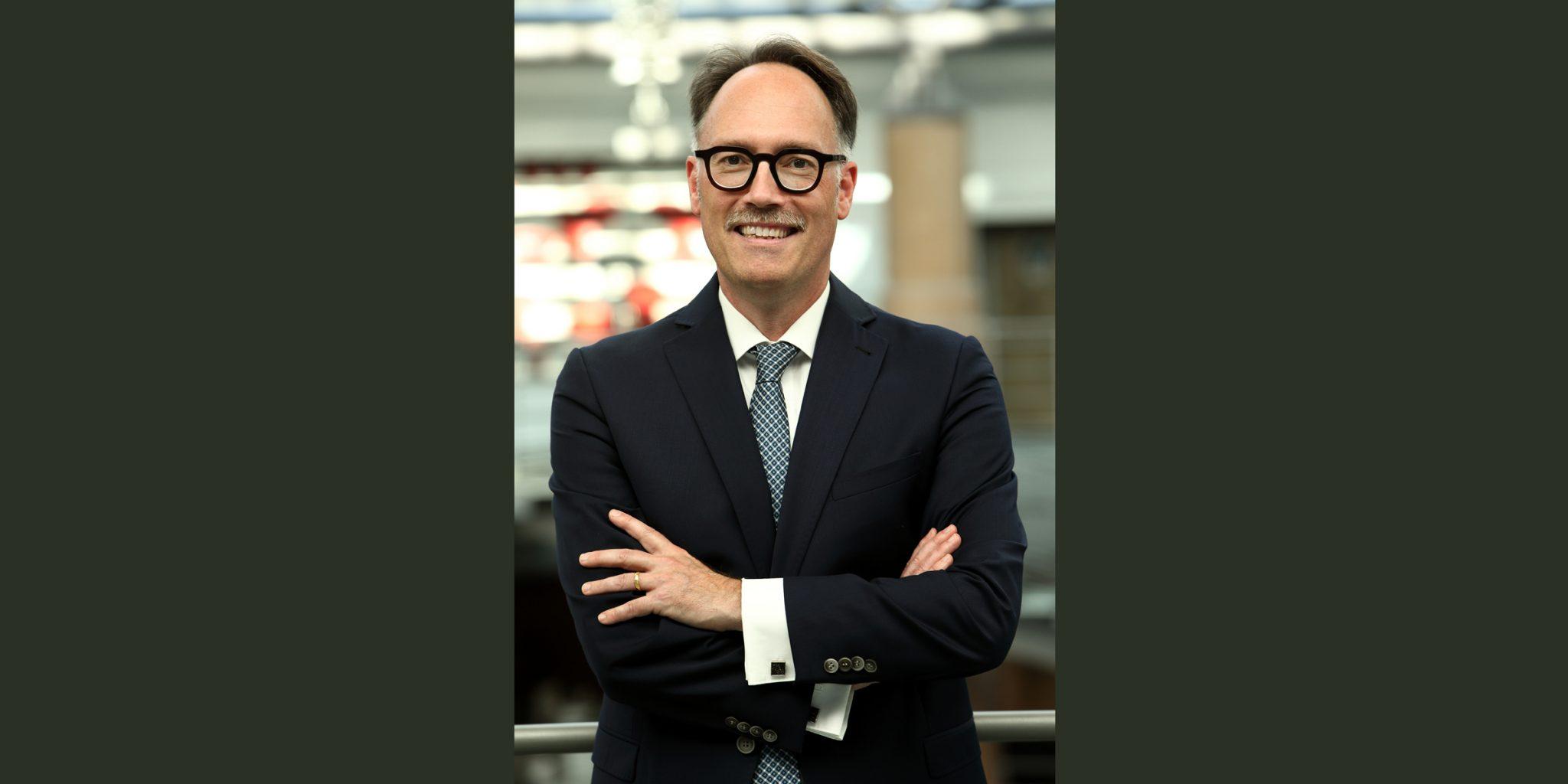 Farbporträt eines freundlich lächelnden Mannes von der Deutsche Bank Luxemburg mit auffälliger, schwarzer Brille, der in einem eleganten, dunklen Business-Anzug und mit überkreuzten Armen posiert.