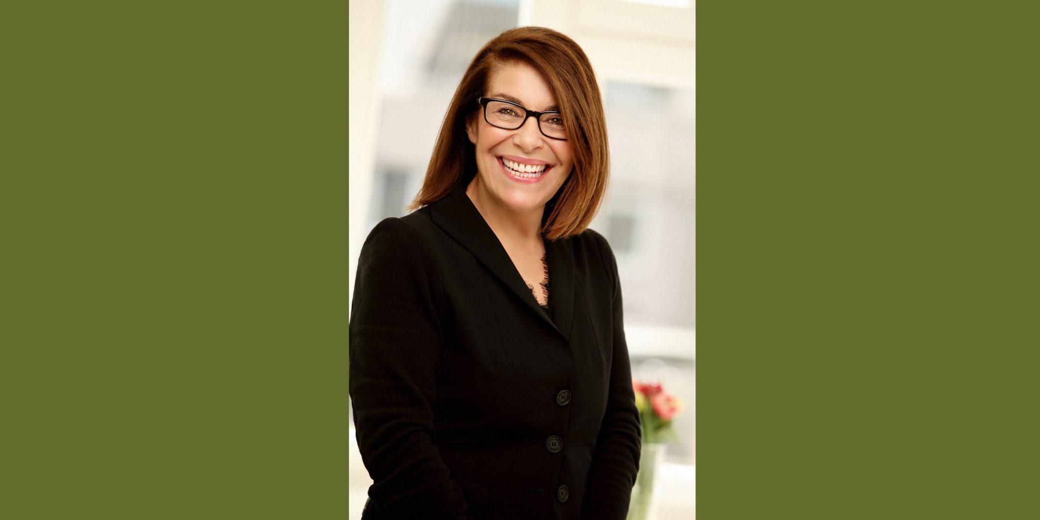 Farbportrait einer breit lächelnden Frau von der Agentur Moccamedia mit dunkler Brille, die in einem schwarzen Business-Dress seitlich posiert.