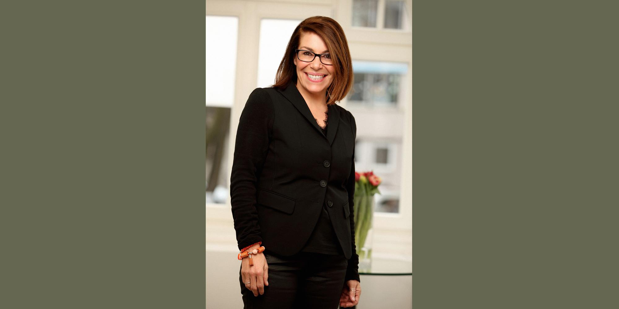 Farbportrait einer Frau mit schwarzer Brille von der Agentur Moccamedia, die stehend und breit lächelnd mit herabhängenden Armen posiert.