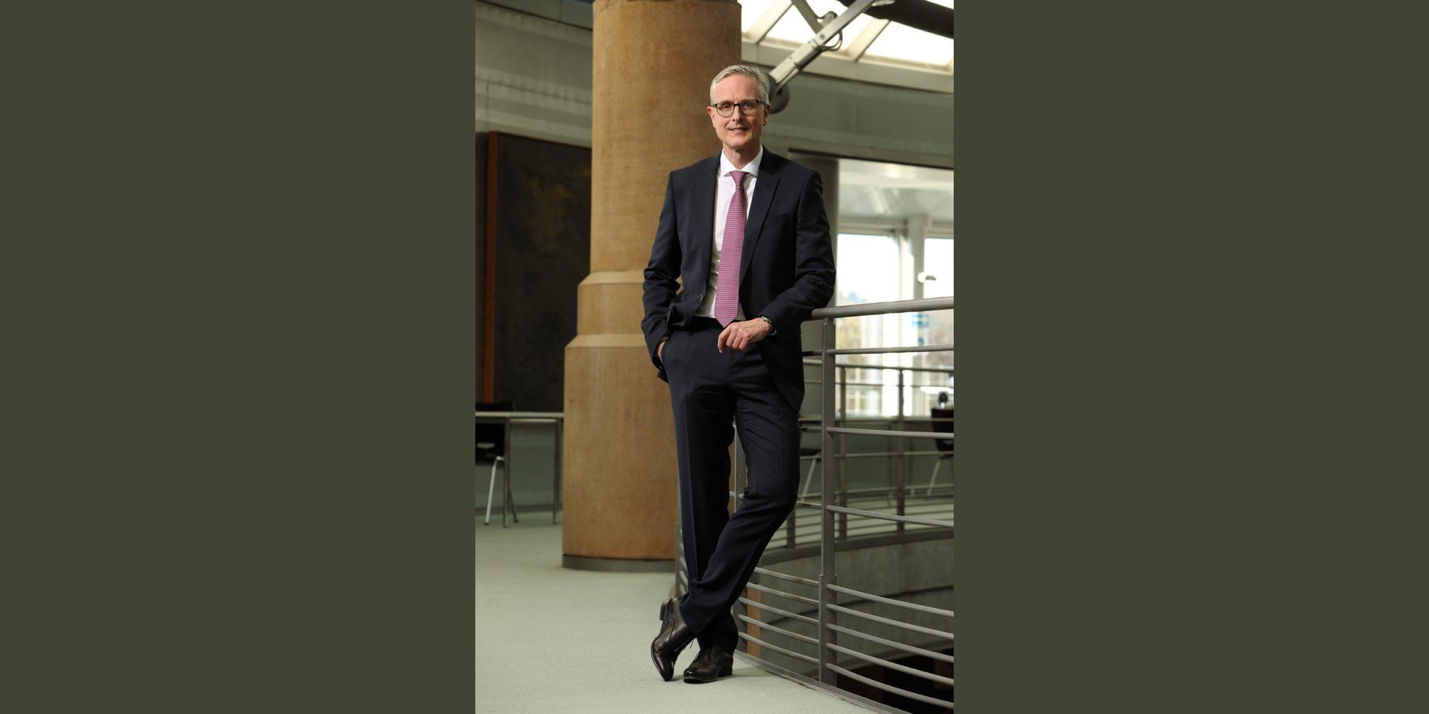 Ganzkörperportrait in Farbe von einem Mann in elegantem Business-Anzug, der lässig am Stahlgeländer einer modernen Treppe, im inneren eines Gebäudes (Deutsche Bank Luxemburg), posiert.