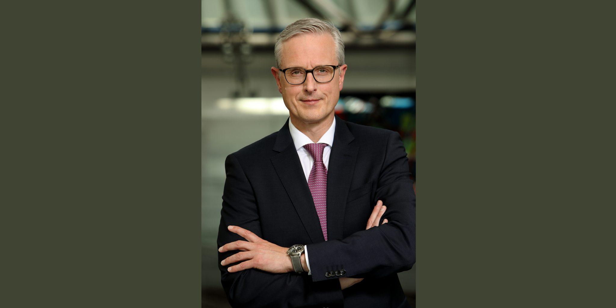 Farbporträt von einem Mann im eleganten Business-Dress (Deutsche Bank Luxemburg), der mit gekreuzten Armen und selbstbewusstem Blick posiert.