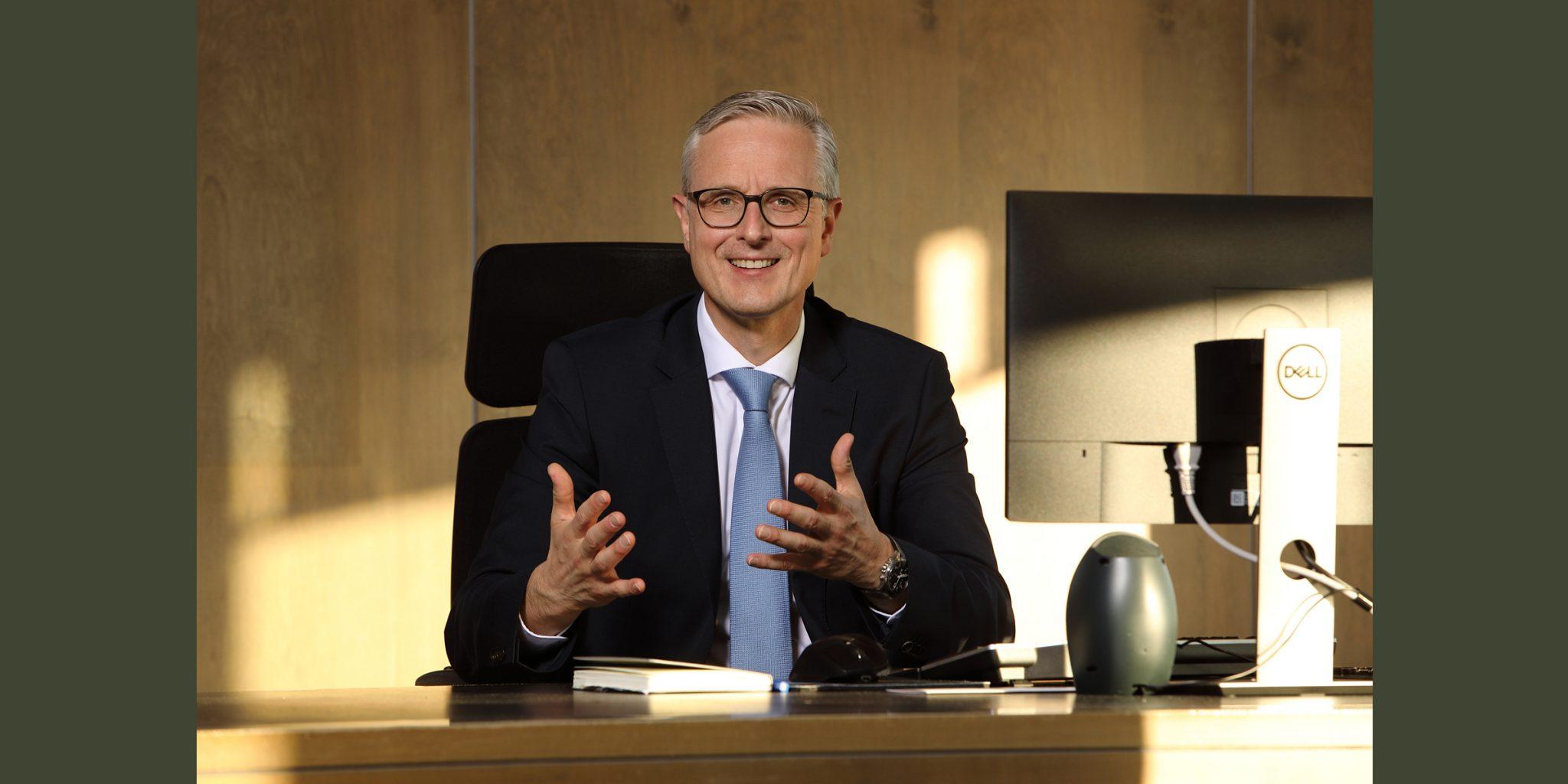 Farbportrait eines souverän lächelnden Mannes, der im Business-Anzug mit hellblauer Krawatte und dunkler Brille an einem Schreibtisch sitzt und, mit den Händen gestikulierend, posiert.