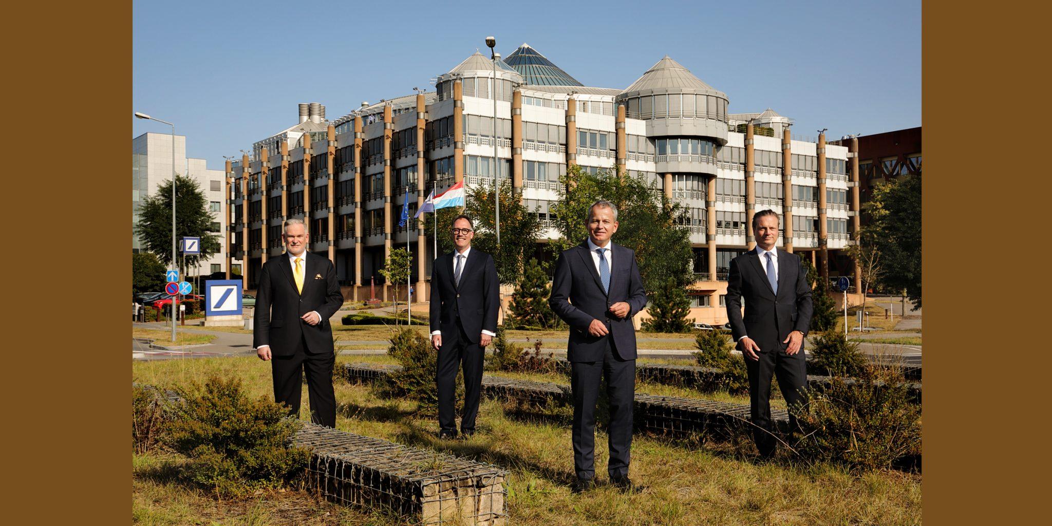 Farbportrait von vier Männern im eleganten Business-Dress, die freundlich lächelnd, in der Grünanlage vor einem imposanten Gebäude (Deutsche Bank Luxemburg) stehend, posieren.