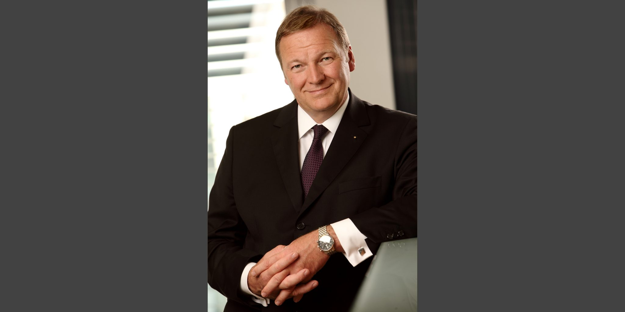 Farbporträt eines Mannes im eleganten, dunklen Business-Anzug von der Nord/LB Luxemburg, der mit verschränkten Händen und freundlich lächelnd posiert.