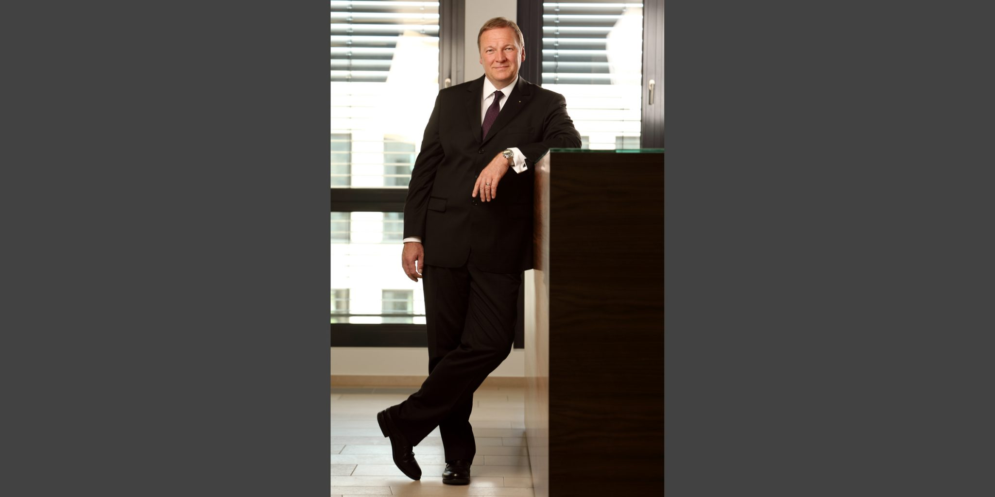 Ganzkörperporträt in Farbe eines Mannes, der in eleganten, dunklen Business-Anzug von der Nord /LB Luxemburg, lässig und mit gekreuzten Beinen an einem Stehpult vor einer Fensterfront posiert.