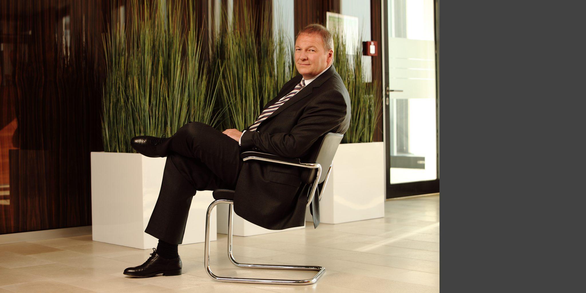 Farbportrait eines Mannes von der Nord/LB Luxemburg im Business-Anzug, der seitlich auf einem Stuhl sitzend, freundlich in die Kamera blickt.