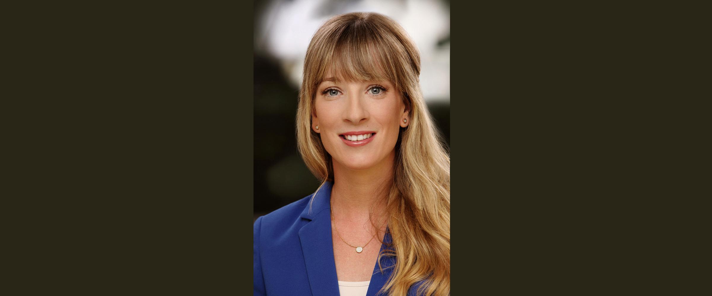 Farbportrait einer blonden Frau in blauem Business-Jackett, die freundlich lächelnd posiert für Bewerbungsfoto..