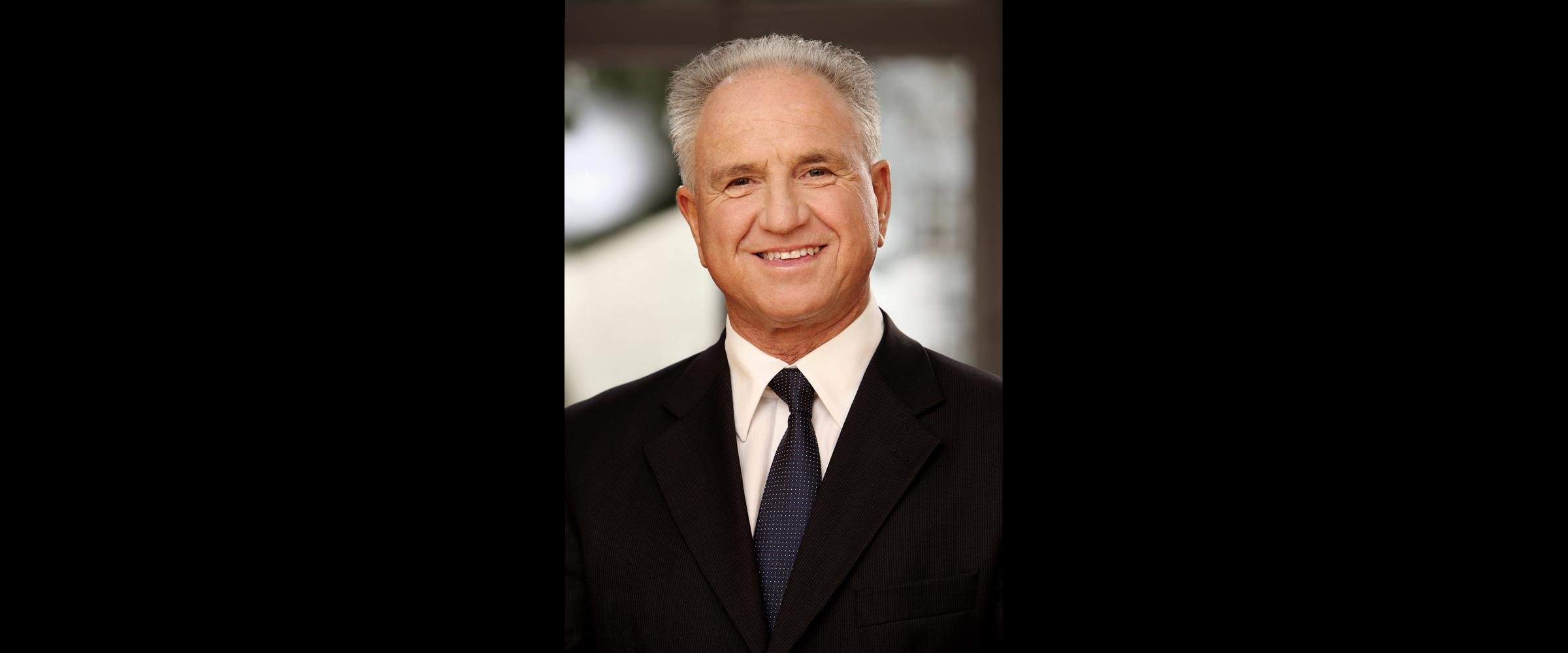 Farbportrait eines älteren, grauhaarigen Mannes in schwarzem Business-Anzug mit Krawatte, der freundlich lächelnd posiert für Bewerbungsfoto und Businessportraits.