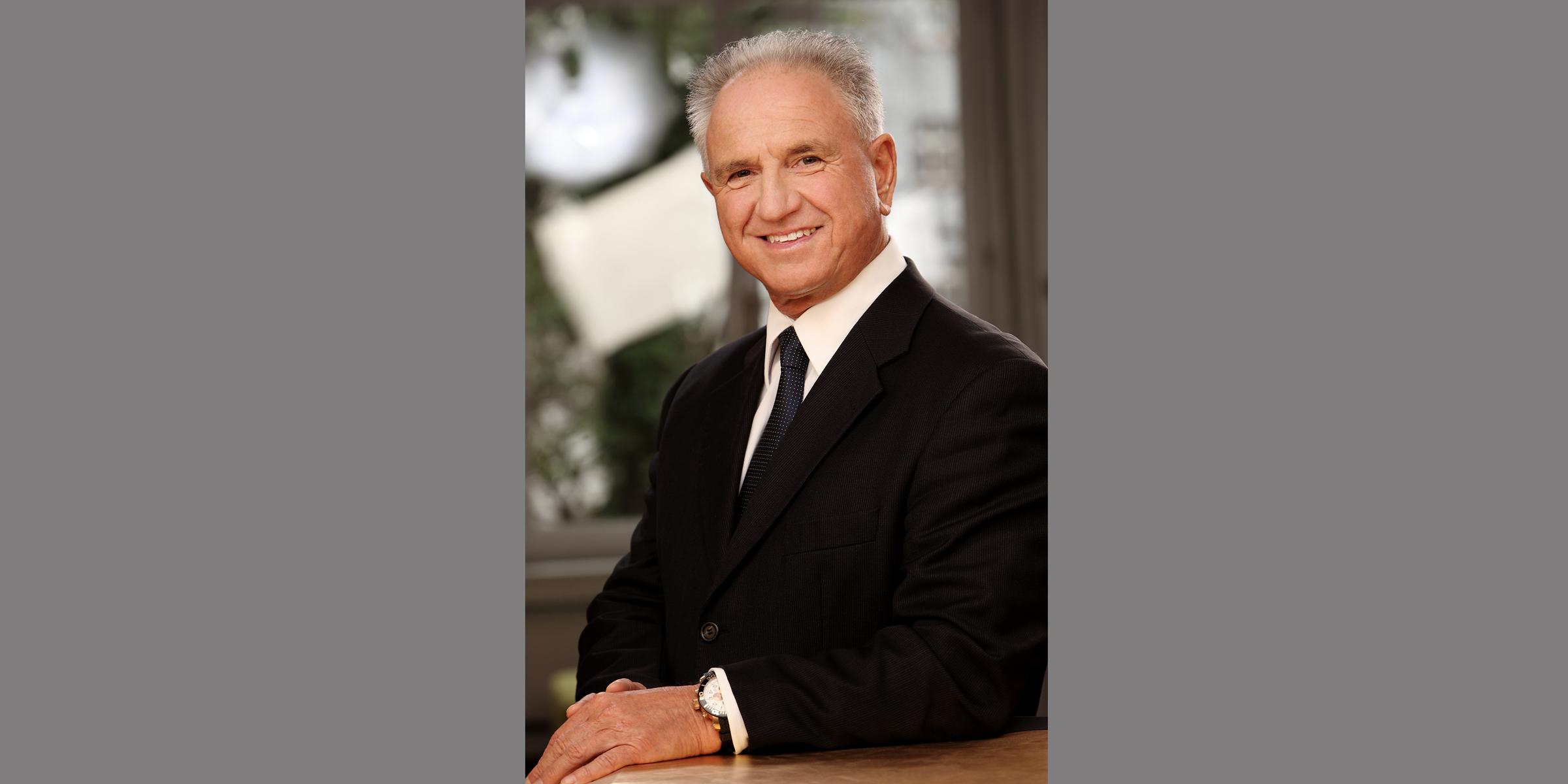 Business Portrait eines älteren, grauhaarigen Mannes in schwarzem Business-Anzug mit Krawatte, der freundlich lächelt und seine Arme seitlich auf einer Tischplatte ablegt.