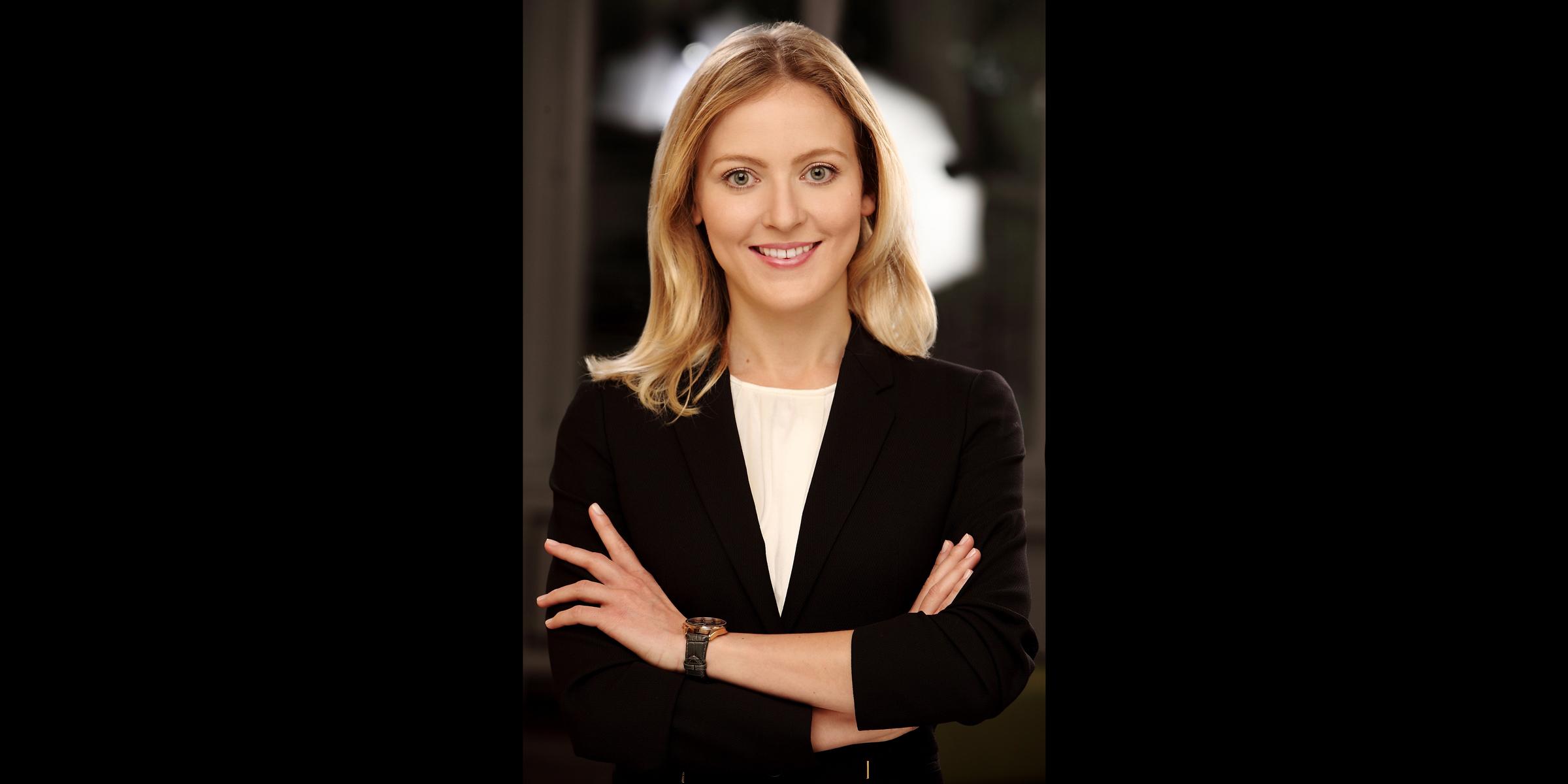 Farbportrait einer blonden Frau mit freundlichem Lächeln, die mit gekreuzten Armen in einem schwarzen Business-Jackett posiert.