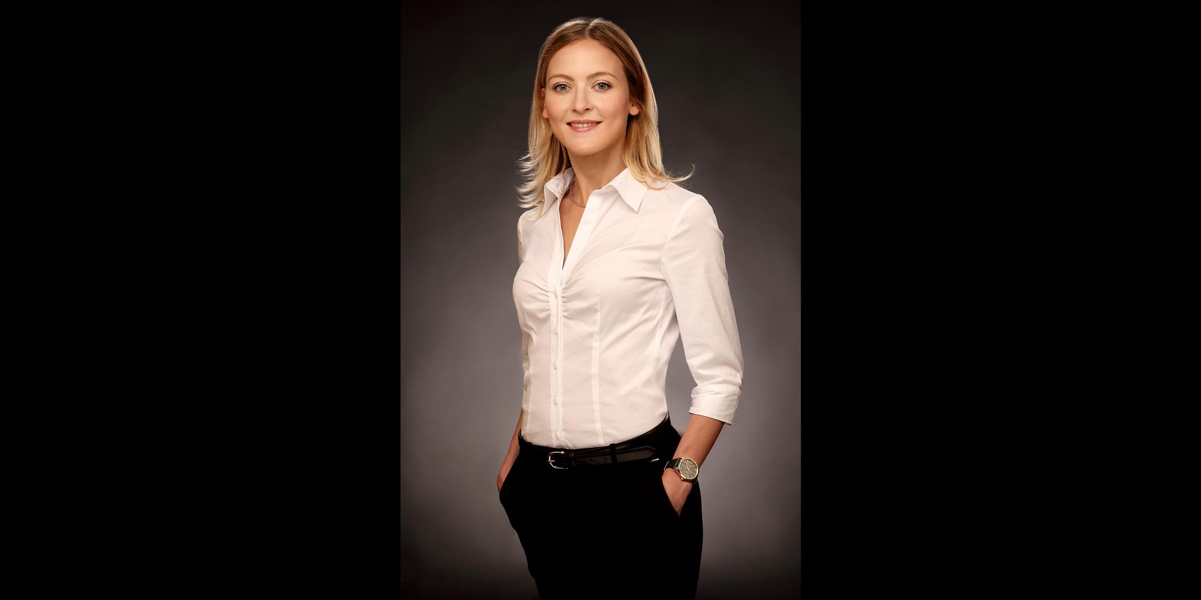 Farbportrait einer blonden Frau mit freundlichem Blick, die in weißer Bluse und dunkler Business-Hose posiert für Business Portrait.
