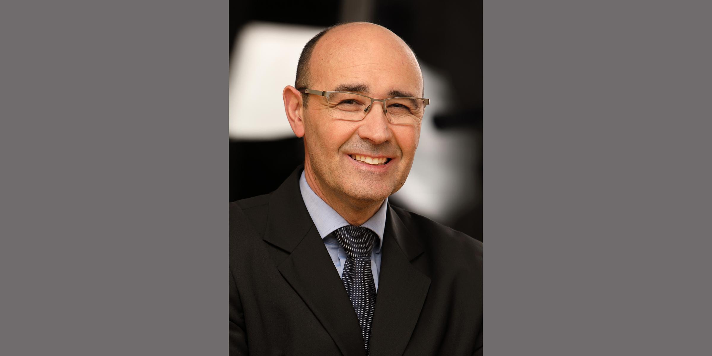 Business Portrait eines älteren Mannes mit freundlichem Lächeln und moderner Brille, der in dunklem Business-Anzug mit Krawatte posiert.