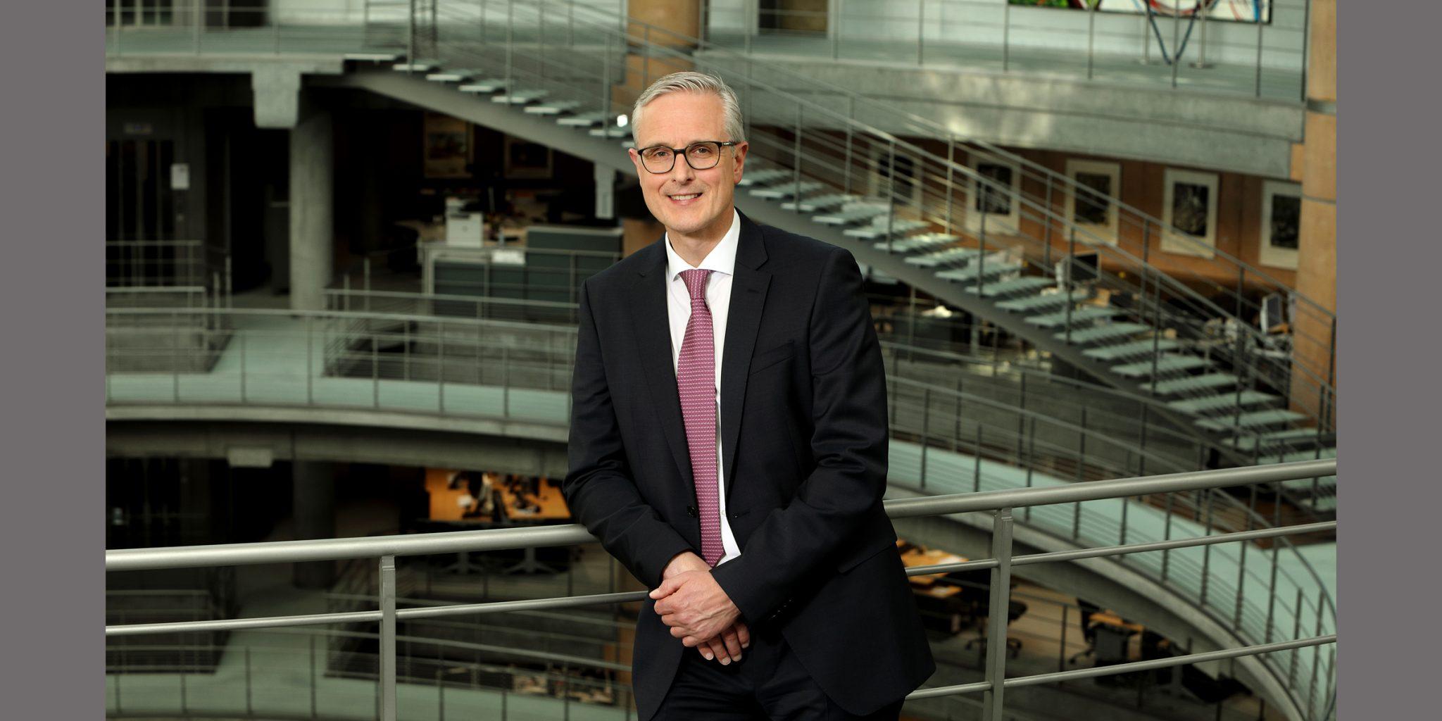 Farbportrait von einem Mann mit dunkler Brille und souveränem Lächeln, der in elegantem Business-Anzug vor einem Gebäude (Deutsche Bank Luxemburg) mit Treppen posiert.