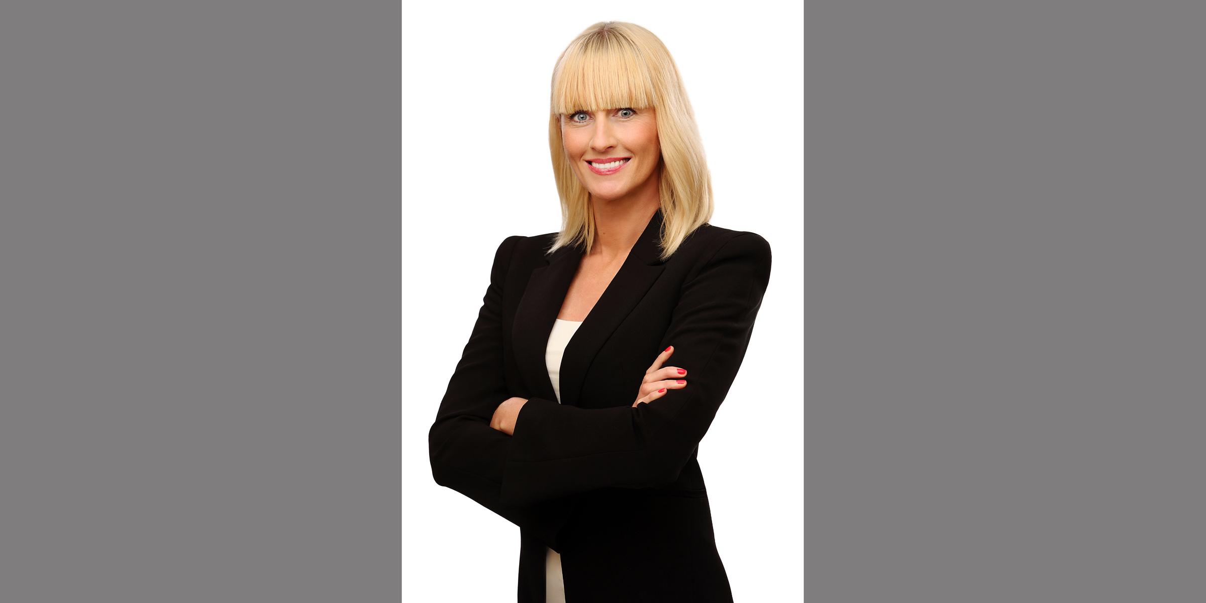 Farbportrait einer blonden Frau mit strahlendem Lächeln, die mit gekreuzten Armen in dunklem Business-Jackett posiert.
