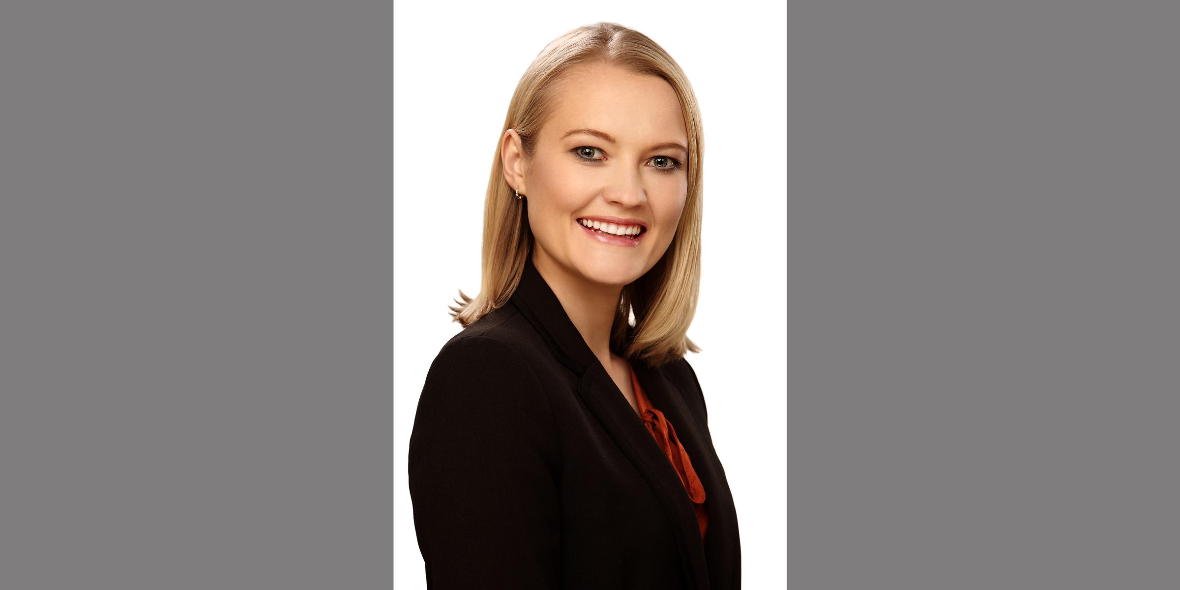 Bewerbungsfoto, Farbportrait einer blonden Frau mit strahlendem Lächeln, die seitlich in dunklem Business-Jackett posiert.