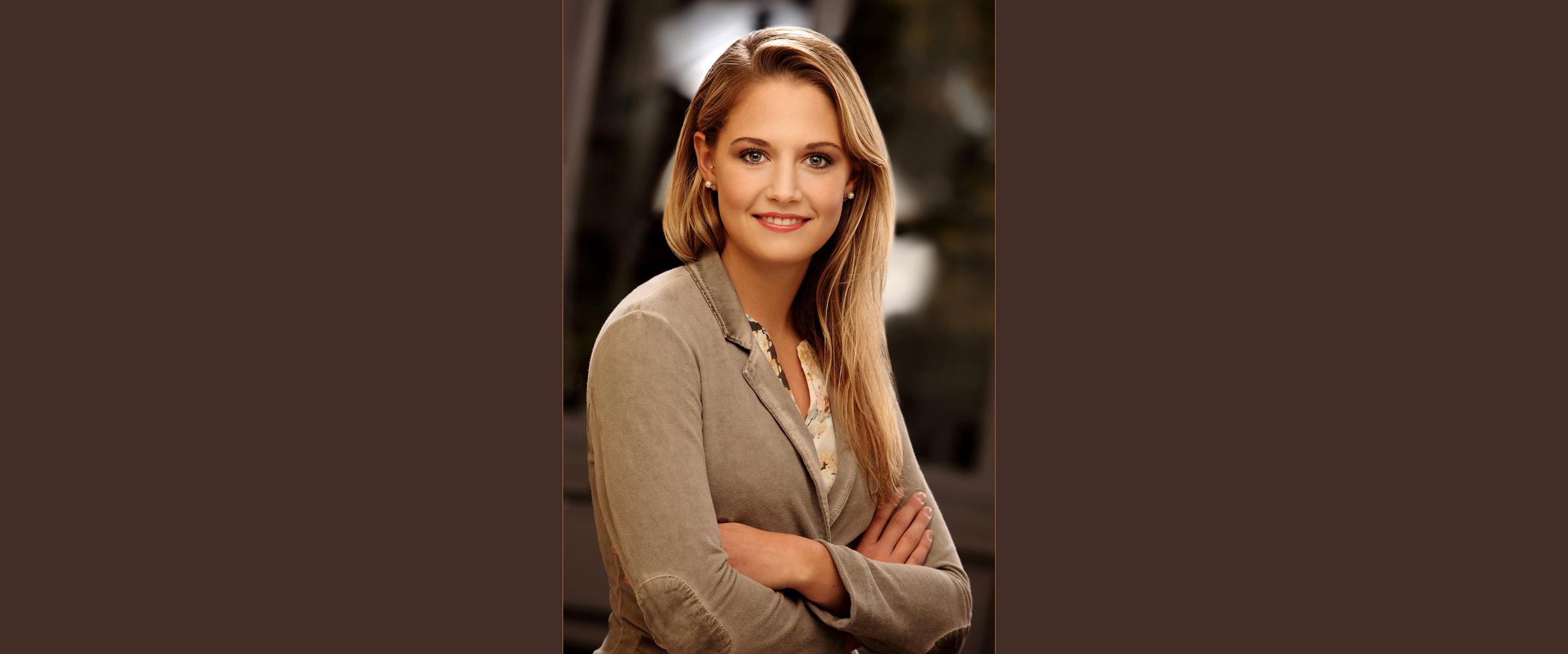 Bewerbungsfoto, Farbportrait einer jungen, blonden Frau mit freundlichem Gesichtsausdruck in legerem Jackett, die ihre Arme vor der Brust kreuzt.