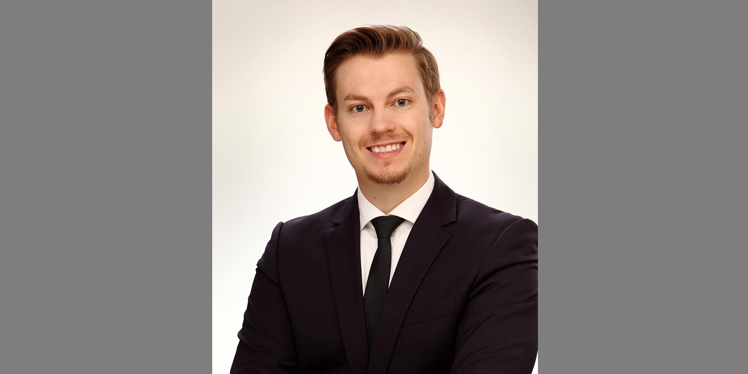Business Portrait eines freundlich lächelnden Mannes, der in schwarzem Business-Anzug mit Krawatte posiert.