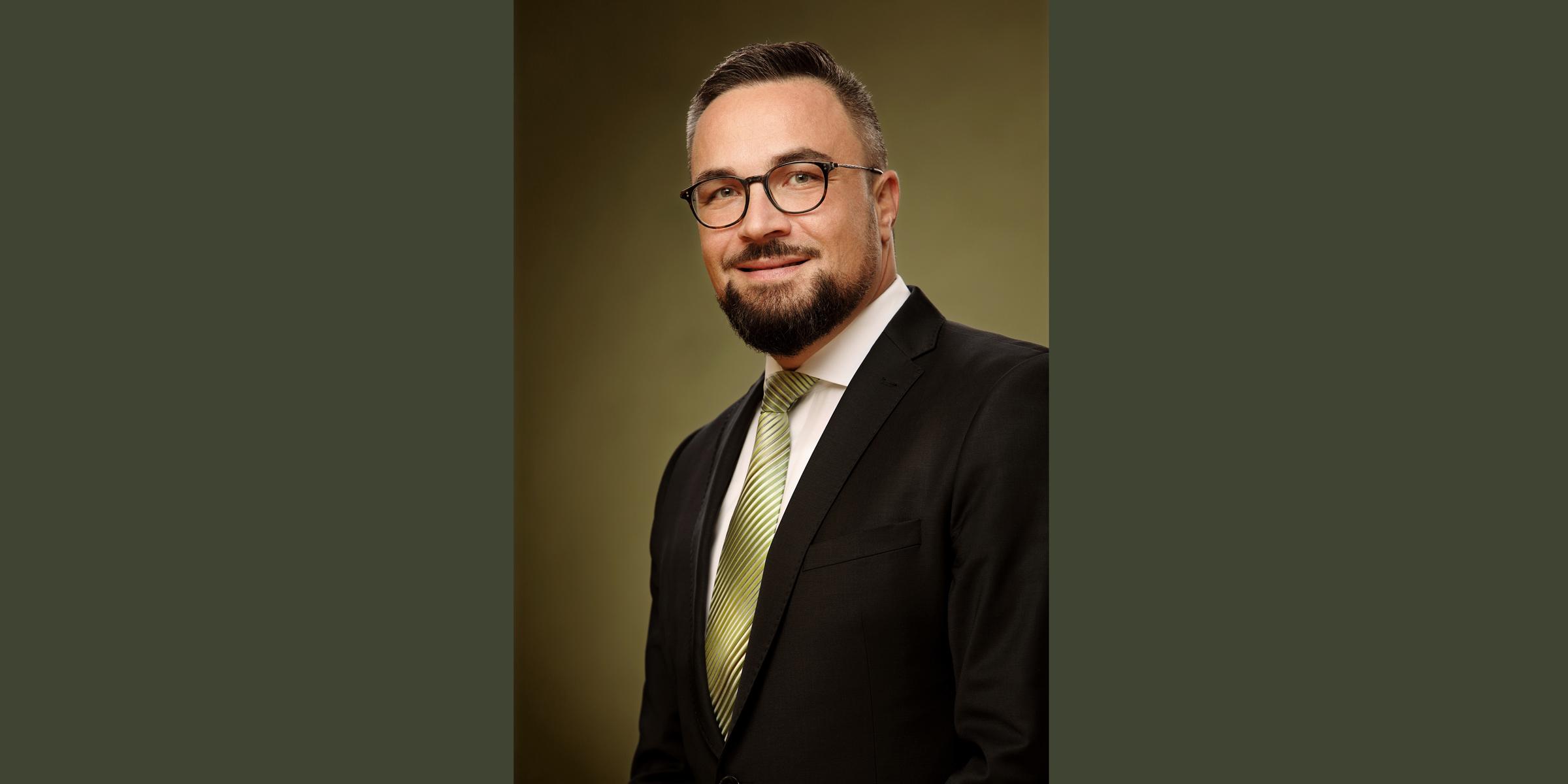Business Portrait eines lächelnden Mannes mit dunkler Brille und Bart, der in schwarzem Business-Anzug mit Krawatte posiert.