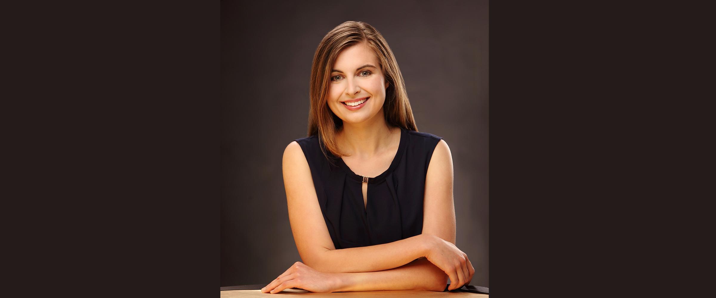 Portrait einer Frau mit freundlichem Lächeln und schwarzer, kurzärmeliger Bluse, die ihre Arme überkreuz auf einer Tischplatte ablegt.