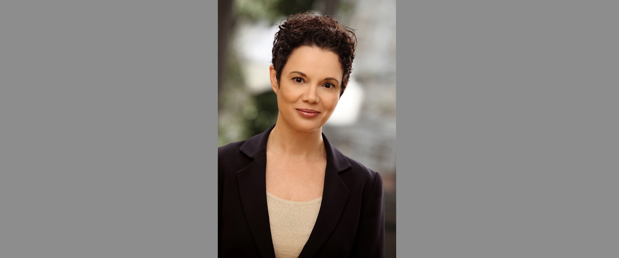 Farbportrait einer Frau mit dunklem, kurzen Haar und freundlichem Gesichtsausdruck, die in einem schwarzen Business-Jackett posiert.