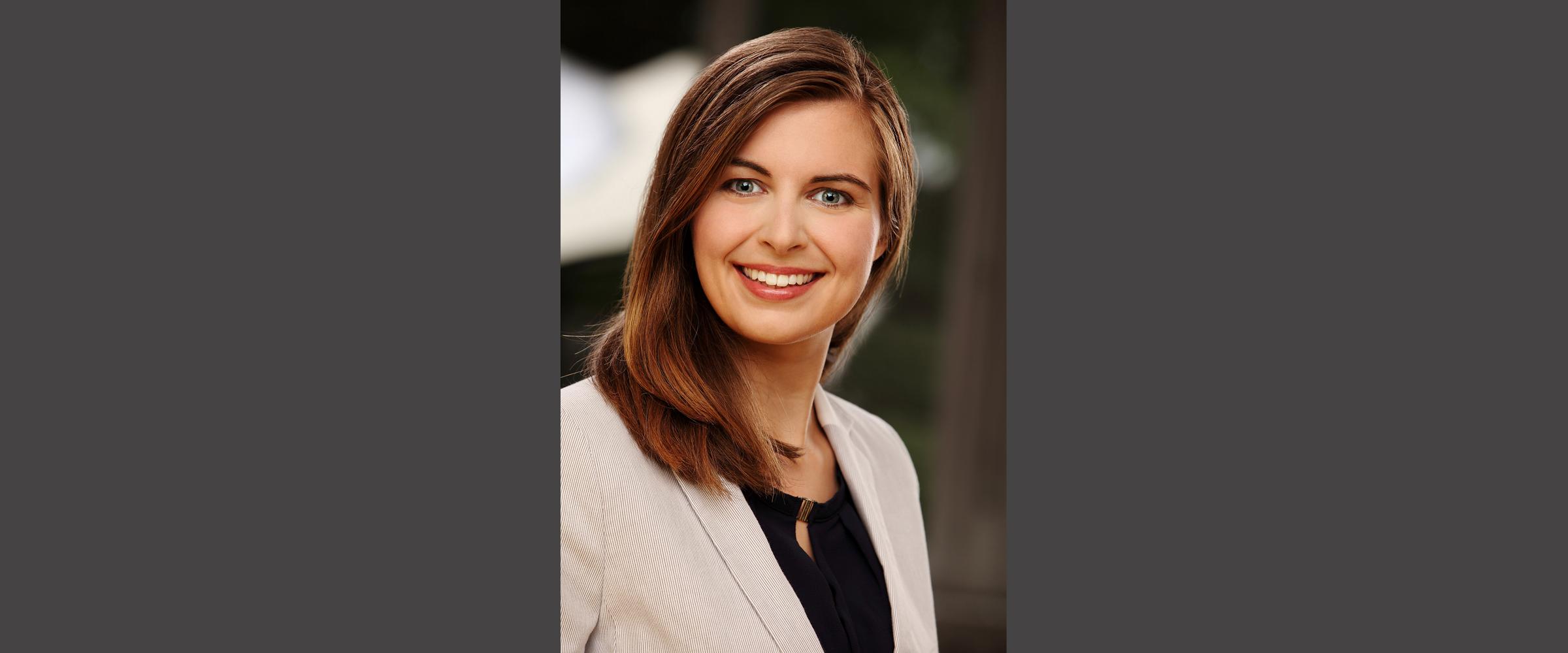 Bewerbungsfoto, Farbportrait einer Frau in hellem Jackett, mit freundlichem Gesichtsausdruck und einem strahlenden Lächeln.