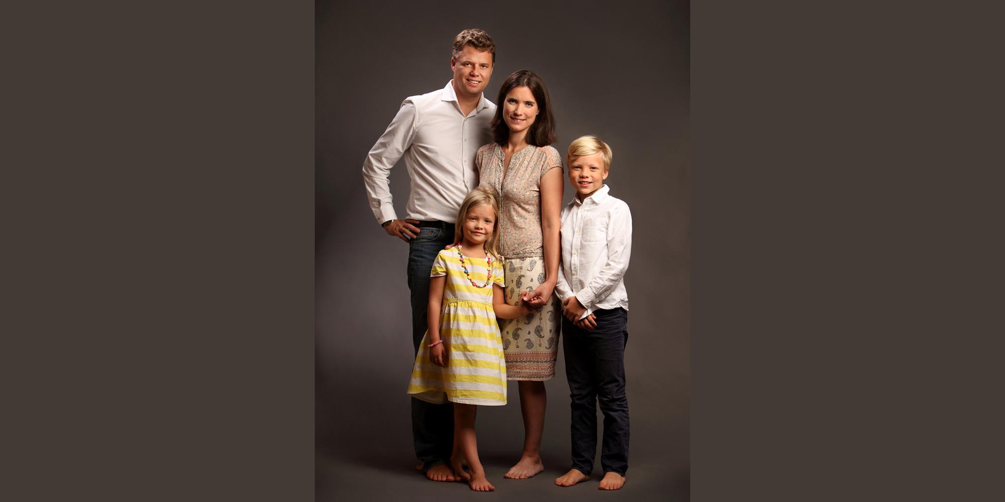 Ganzkörperportrait eines Mannes, einer dunkelhaarigen Frau, einem größeren Jungen und einem kleinen, blonden Mädchen in gestreiftem Sommerkleid, die alle barfuß dicht beieinander stehen und freundlich schauen (Familienportrait).
