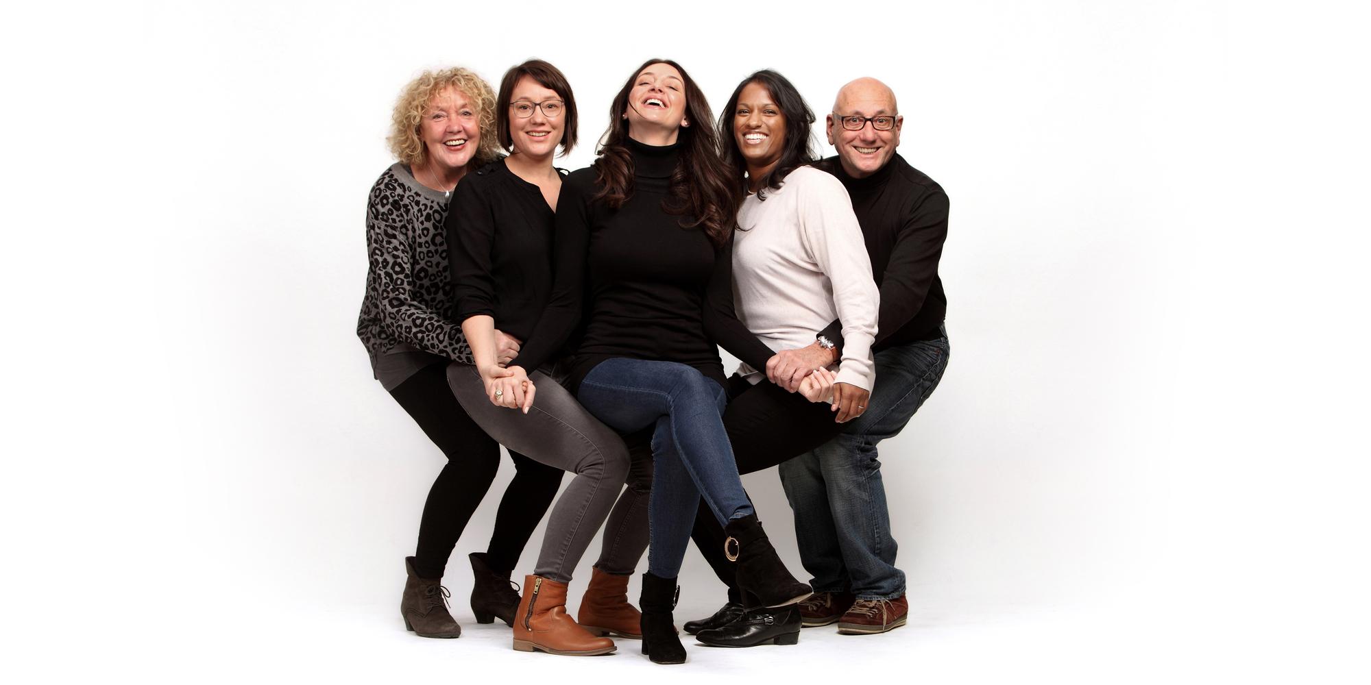 Farbportrait von vier Frauen und einem Mann, die fröhlich lachen und ihre Knie und Arme verschränkt halten, um eine sitzende Position einzunehmen.