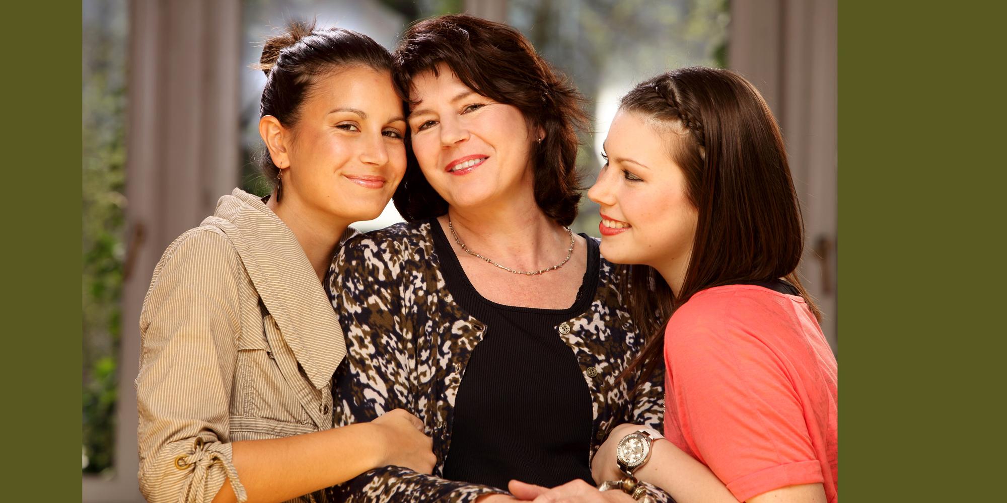 Familien Portrait einer älteren, dunkelhaarigen Frau, die lächelt und links und rechts von ihr sieht man zwei junge, freundlich schauende Frauen, die sich unter ihren Armen einhaken.