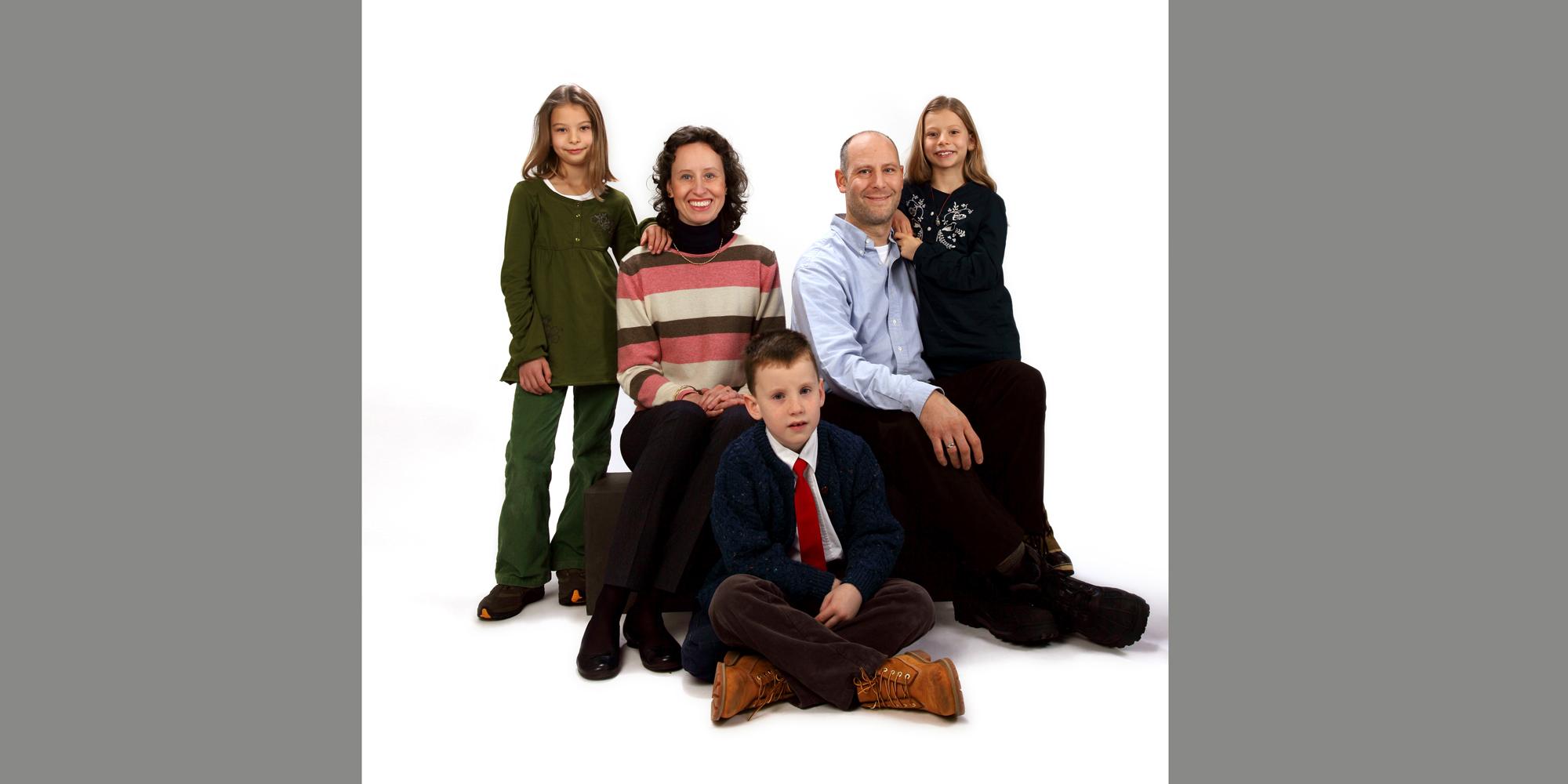 Ganzkörperportrait (Familienfoto) in Farbe von einem Mann und einer Frau, die nebeneinander sitzen, zwei Mädchen, die ihre Hände auf deren Schulter ablegen und einem kleinen Jungen mit roter Krawatte, der davor auf dem Boden im Schneidersitz posiert.