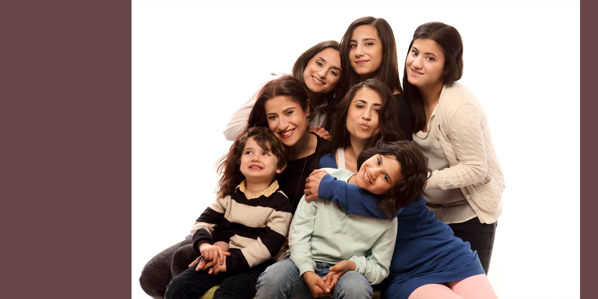 Farbportrait von vier dunkelhaarigen, lächelnden Frauen, die ihre Köpfe dicht beieinander halten und vor sich zwei kleinere Kinder im Arm halten.