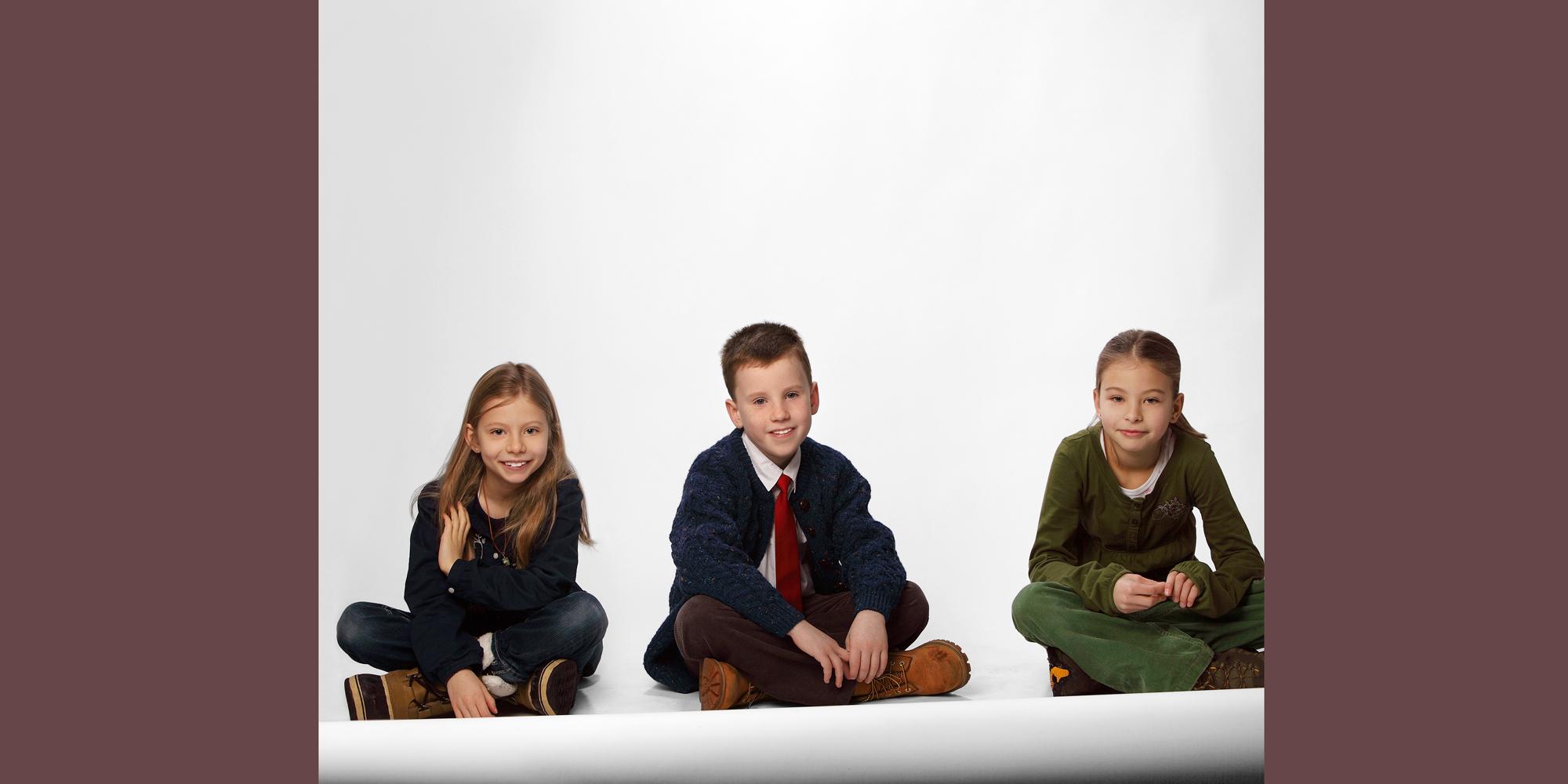 Ganzkörperportrait (Familienfoto) von einem Jungen mit roter Krawatte, der im Schneidersitz auf dem Boden posiert und zwei Mädchen, die lächelnd links und rechts von ihm sitzen.