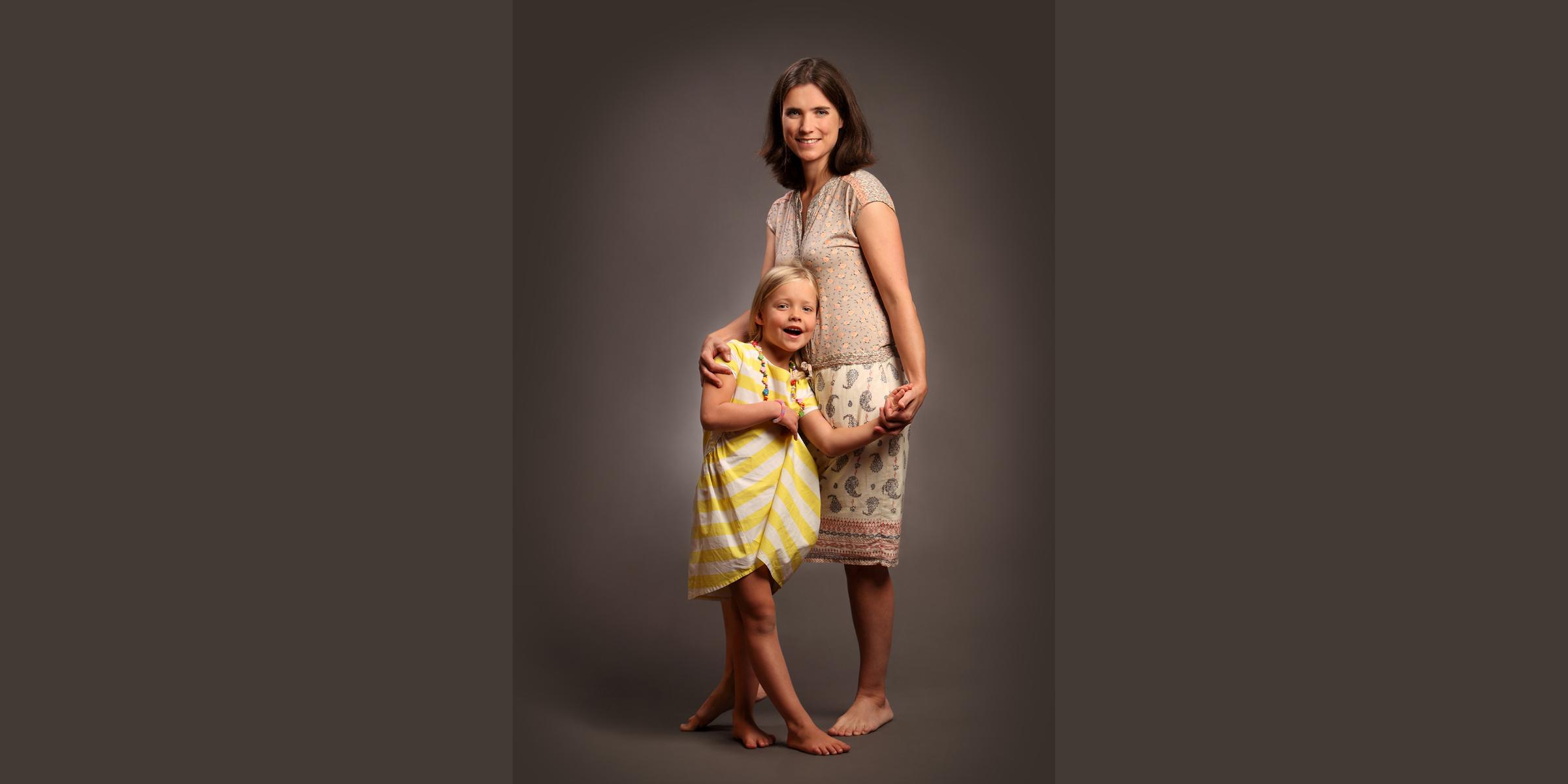 Ganzkörperportrait in Farbe von einer Frau in sommerlicher Kleidung, die ein kleines, blondes Mädchen umarmt, das in einem gelbgestreiften Kleid vor ihr für Familienfoto steht.