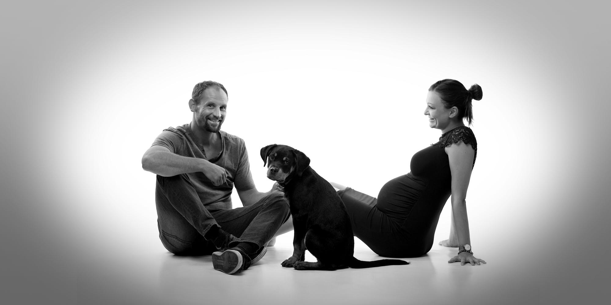 Schwarz-weiß Aufnahme von einem dunkelfarbigen Hund, der traurig schaut und zwischen den Beinen von einer schwangeren Frau und einem Mann für Familienfoto posiert, die seitlich und lächelnd daneben sitzen.