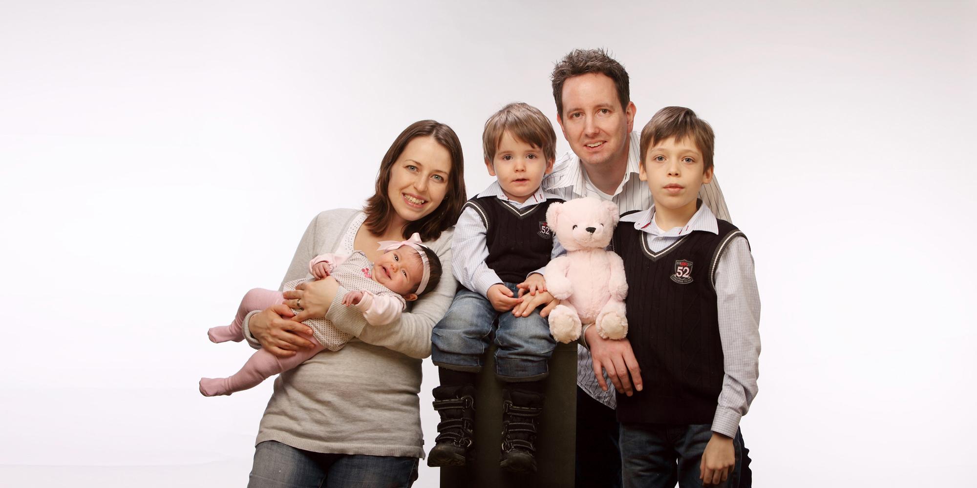 Familienportrait, (Familienfoto) von einer lächelnden Frau, die ein Baby mit Haarschleife auf dem Arm hält, einem Mann der seitlich steht, mit Teddy in der Hand und einem kleinen Jungen, der zwischen den Beiden, auf einem Hocker sitzend, posiert.